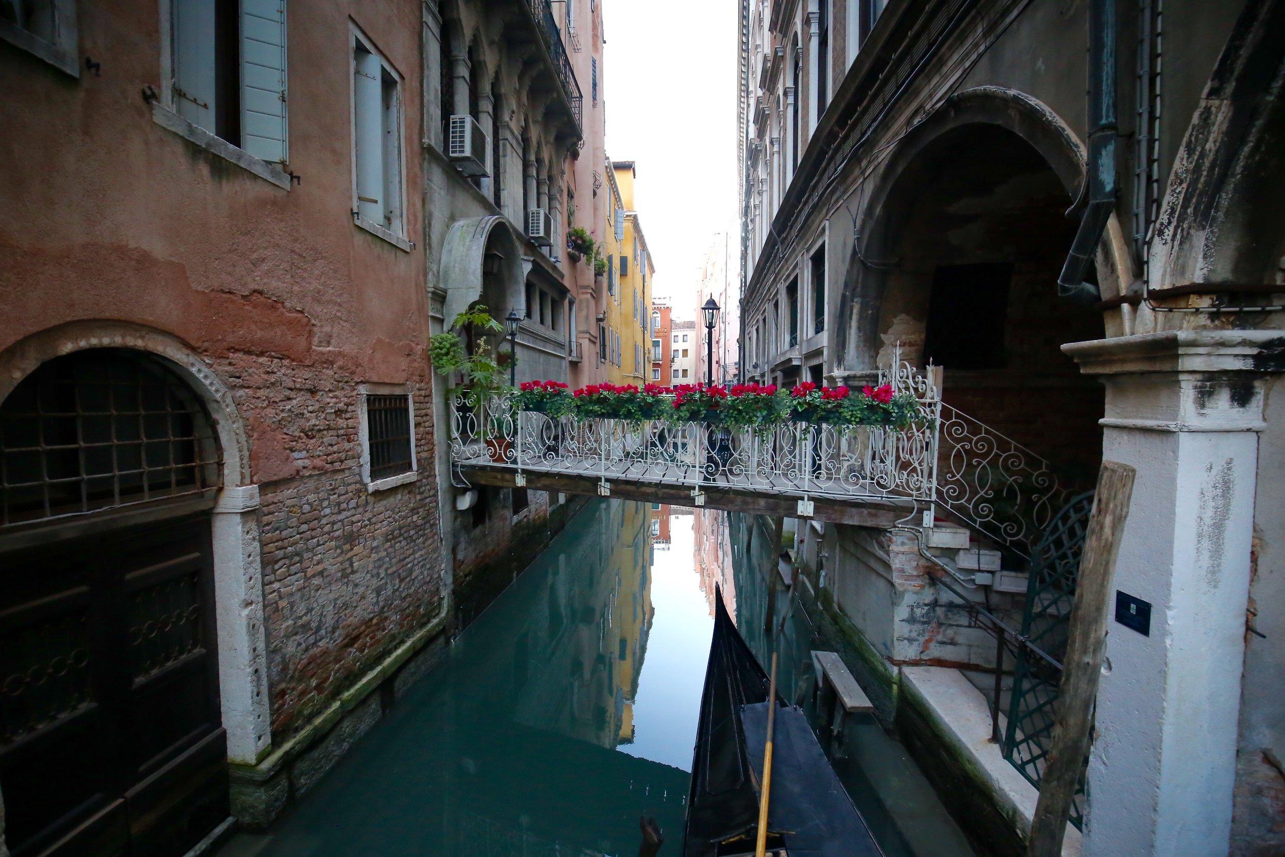 Blue canals and a small bridge with geranium flowerpots, a black gondola underneath, Venice.