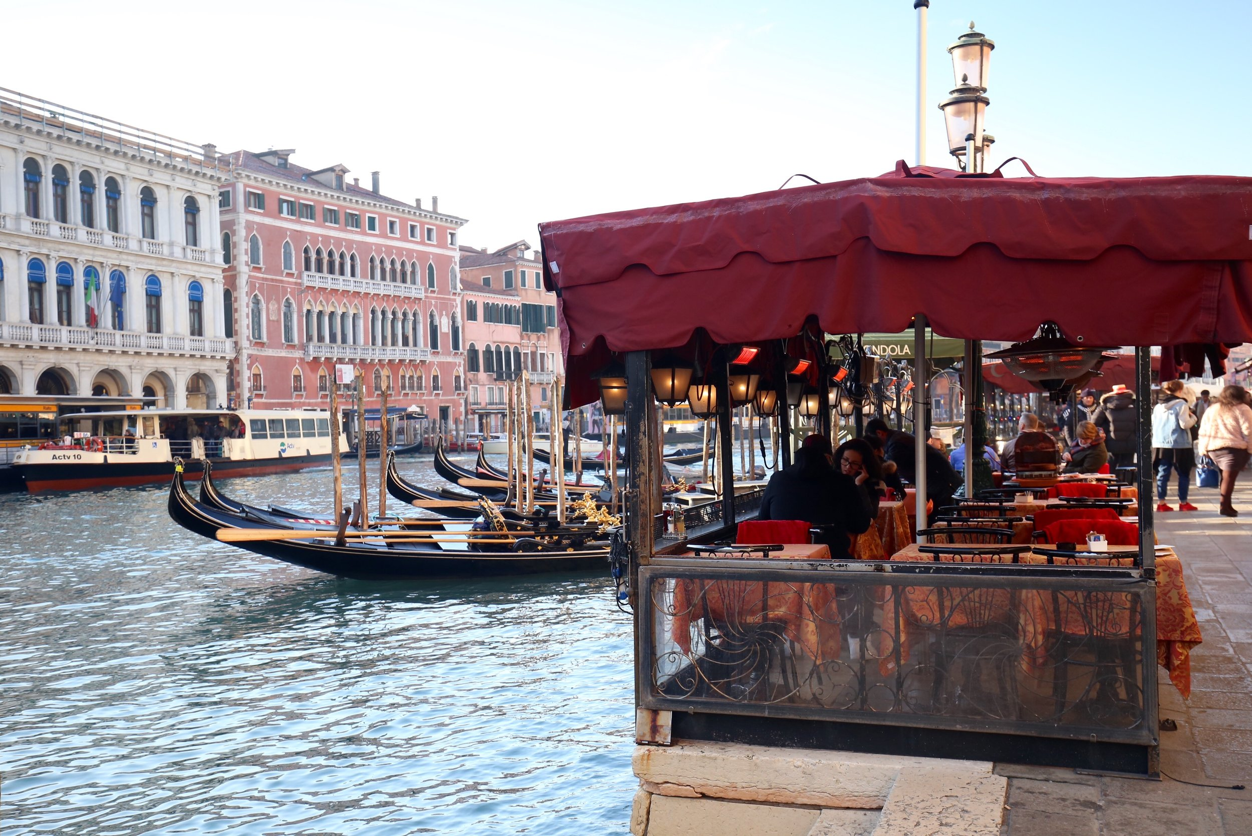 Diners think of what to order in a restaurant by the Grand Canal.
