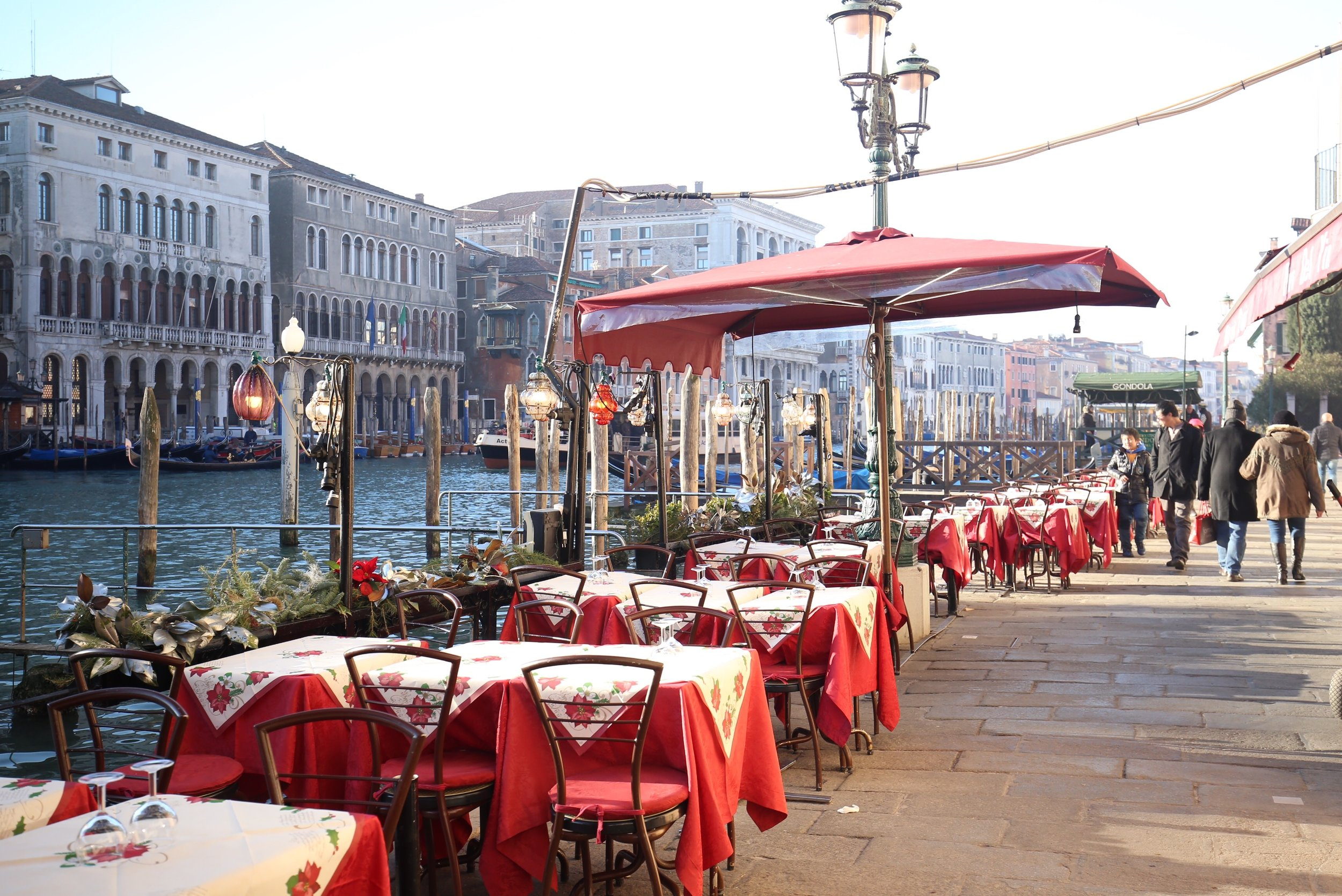 Tables and lanterns are set out by the Grand Canal - with red cloths on them.