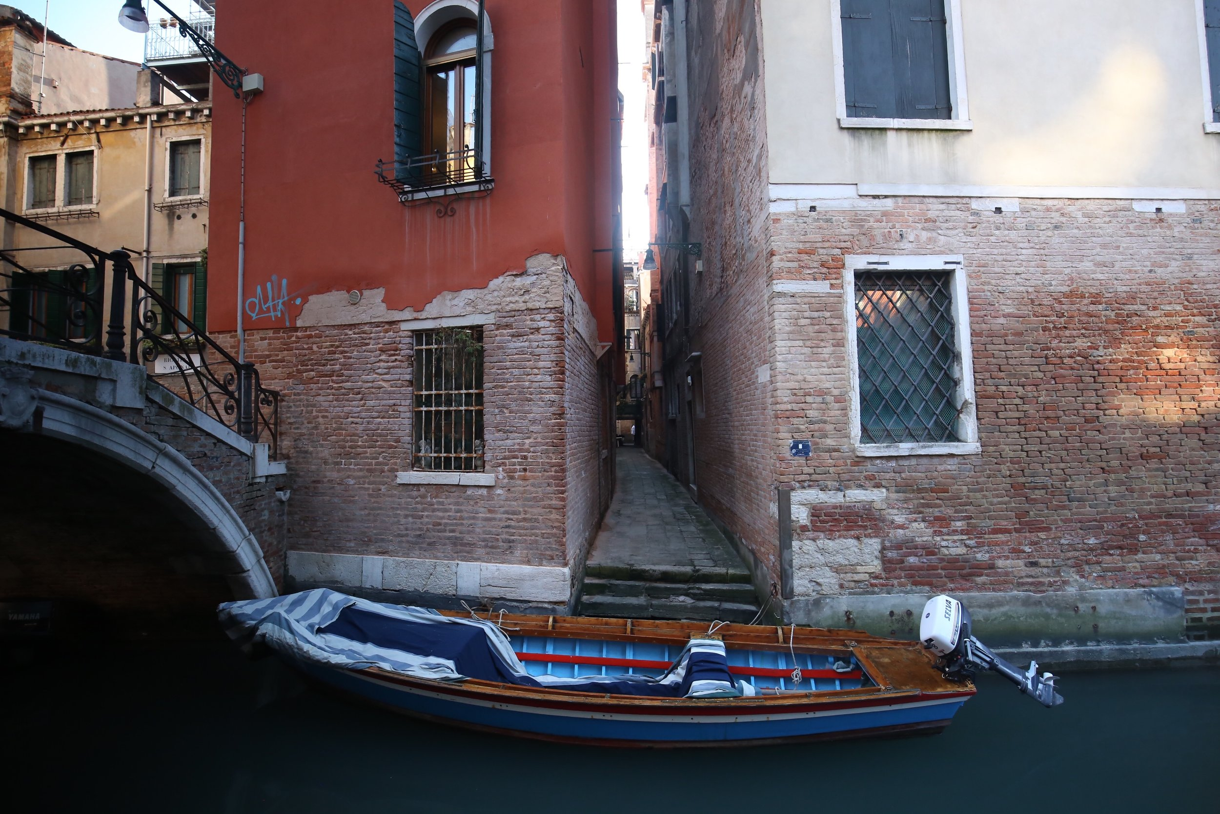 A local's personal boat sits by the canal side under a bridge.