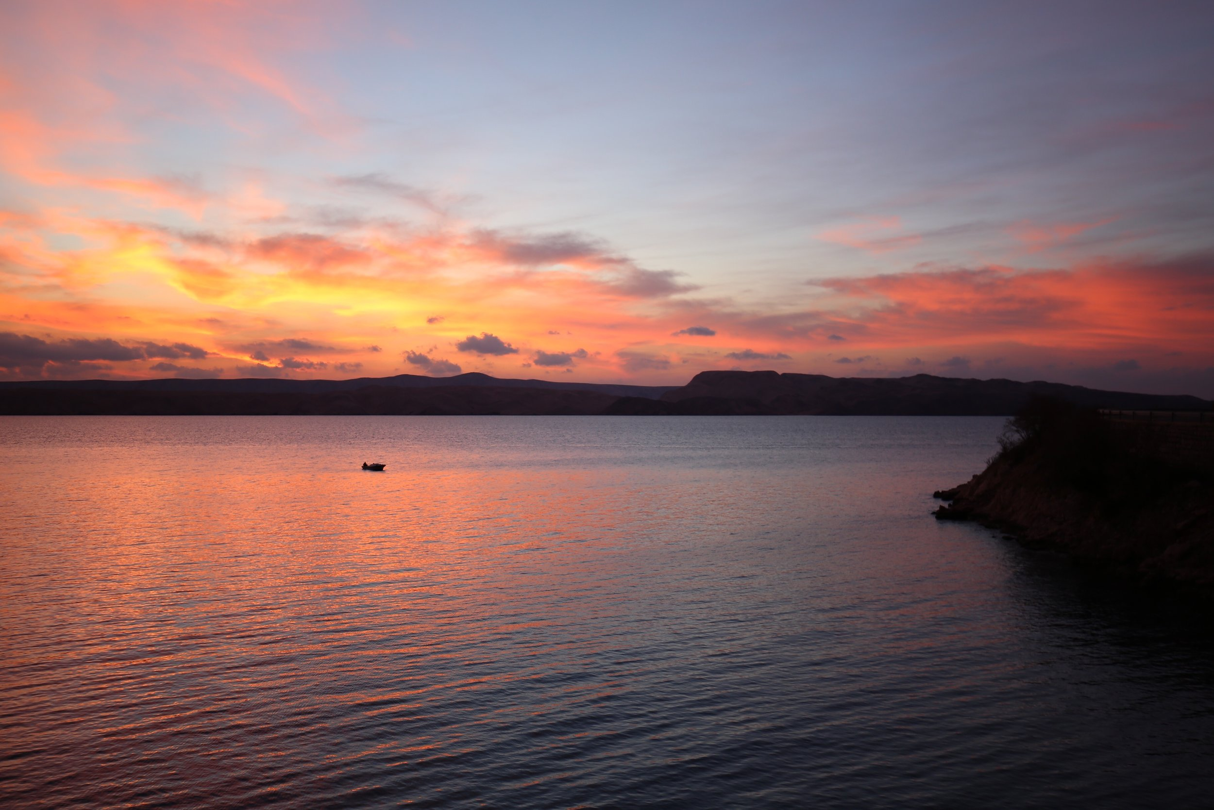 A fishing boat returns to the cove at sunset, Croatia.