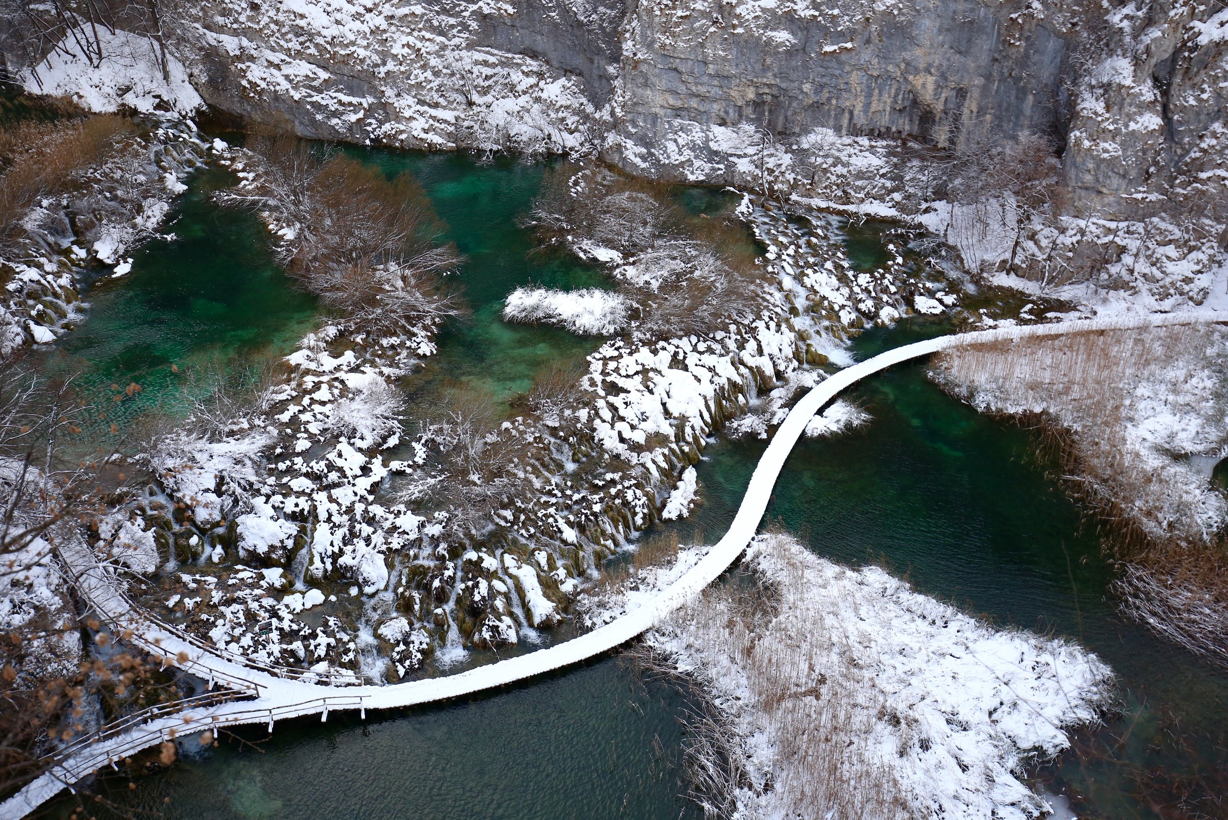 Plitvice National Park in winter - the boardwalks and waterfalls are covered in snow