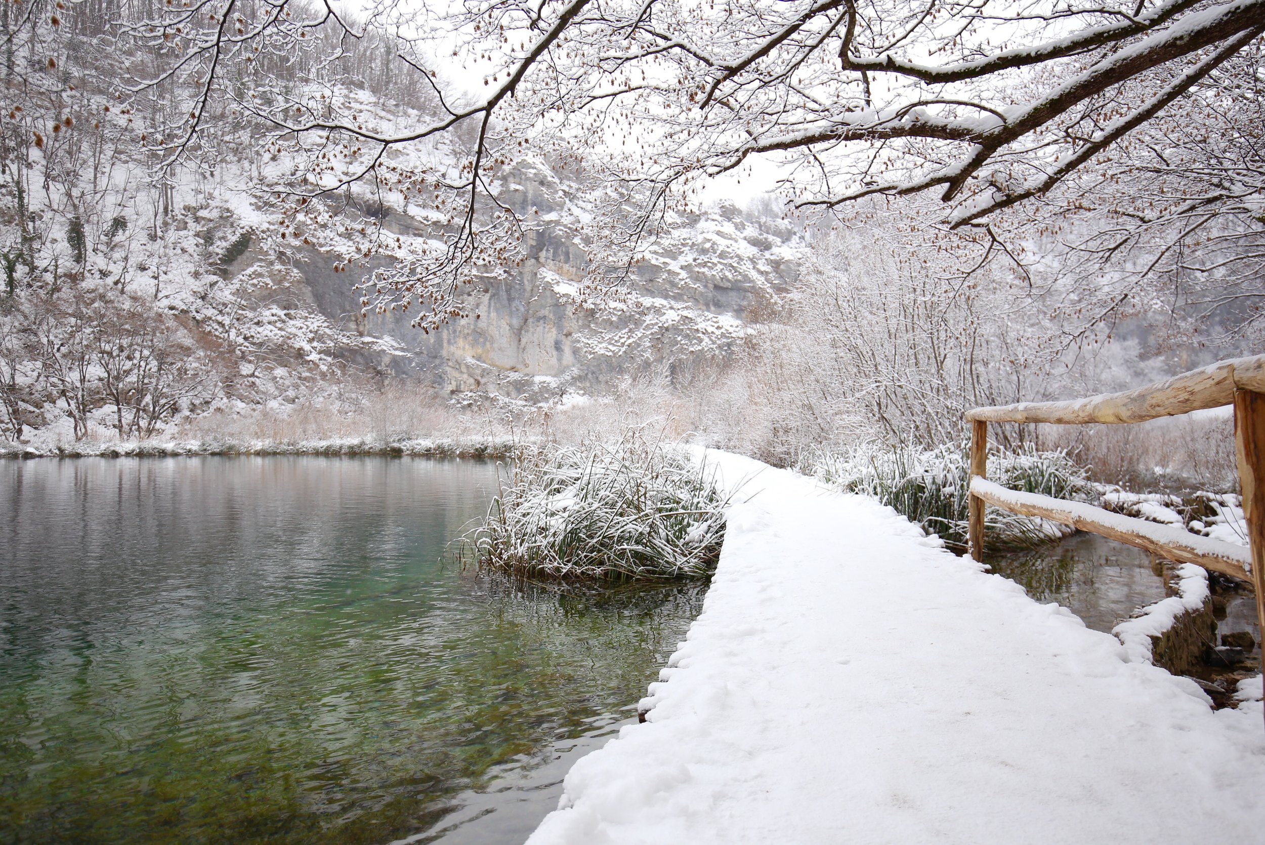 Snow covered boardwalks beside the blue pools of Plitvice lakes in winter.