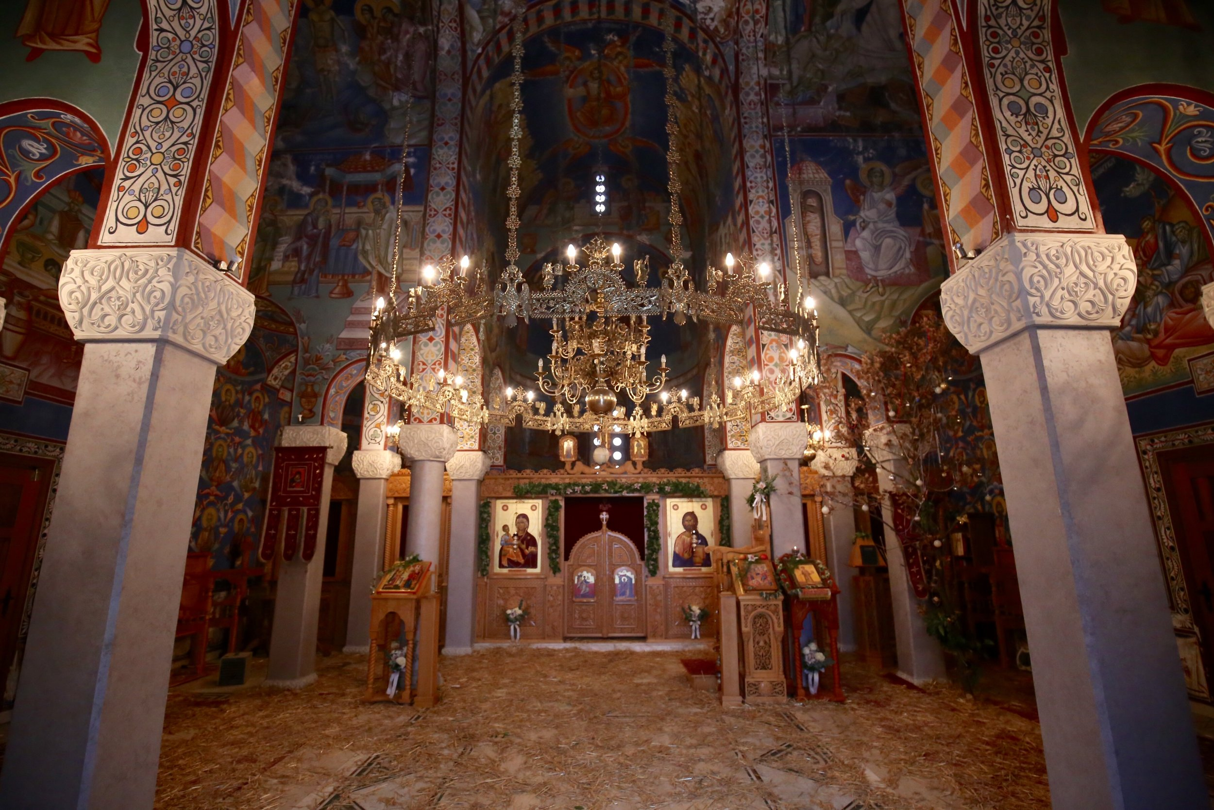 Orthodox Bosnian church interior - painted colours and gold chandelier.