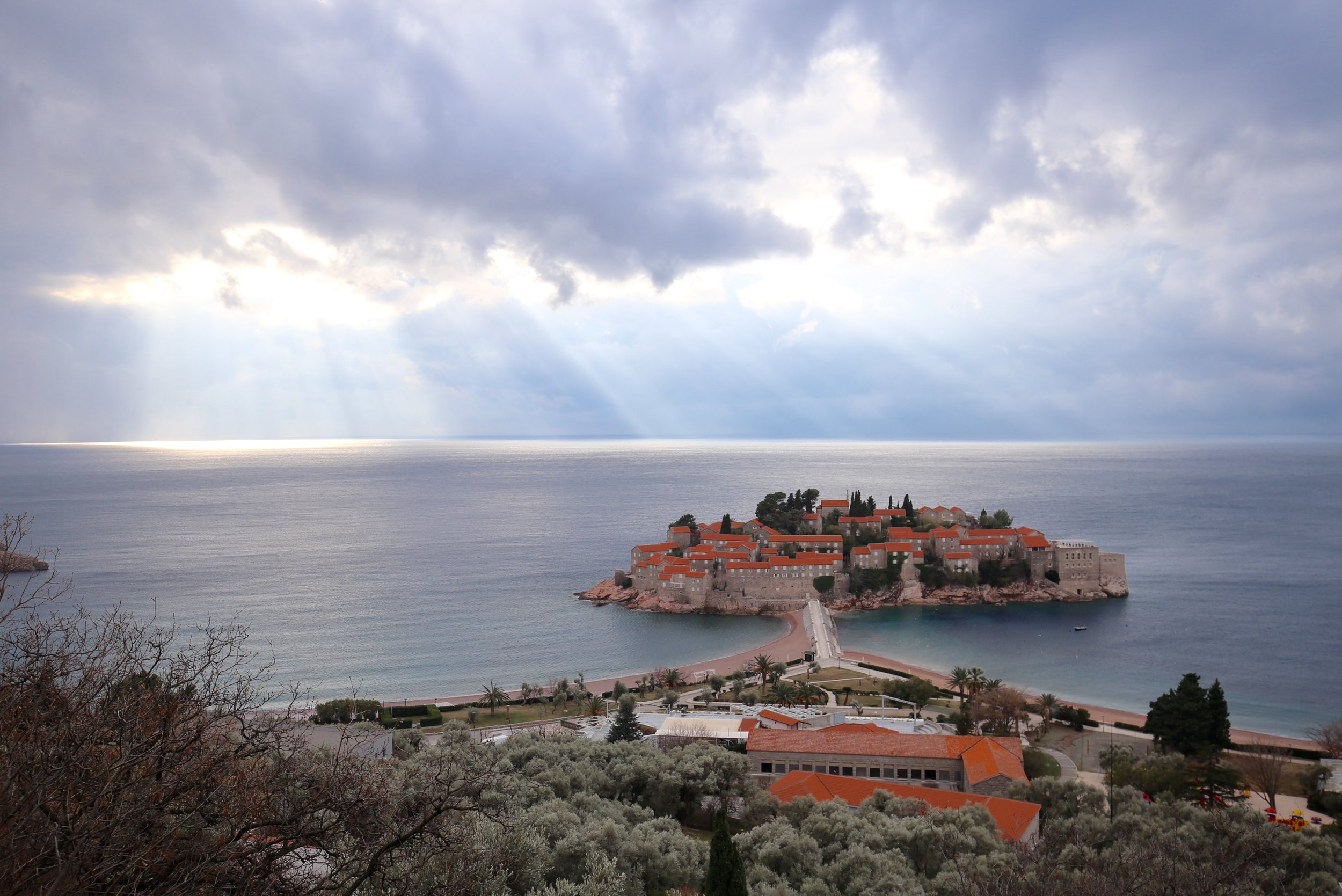 The small island of Sveti Stefan, under the sun's rays, Montenegro.