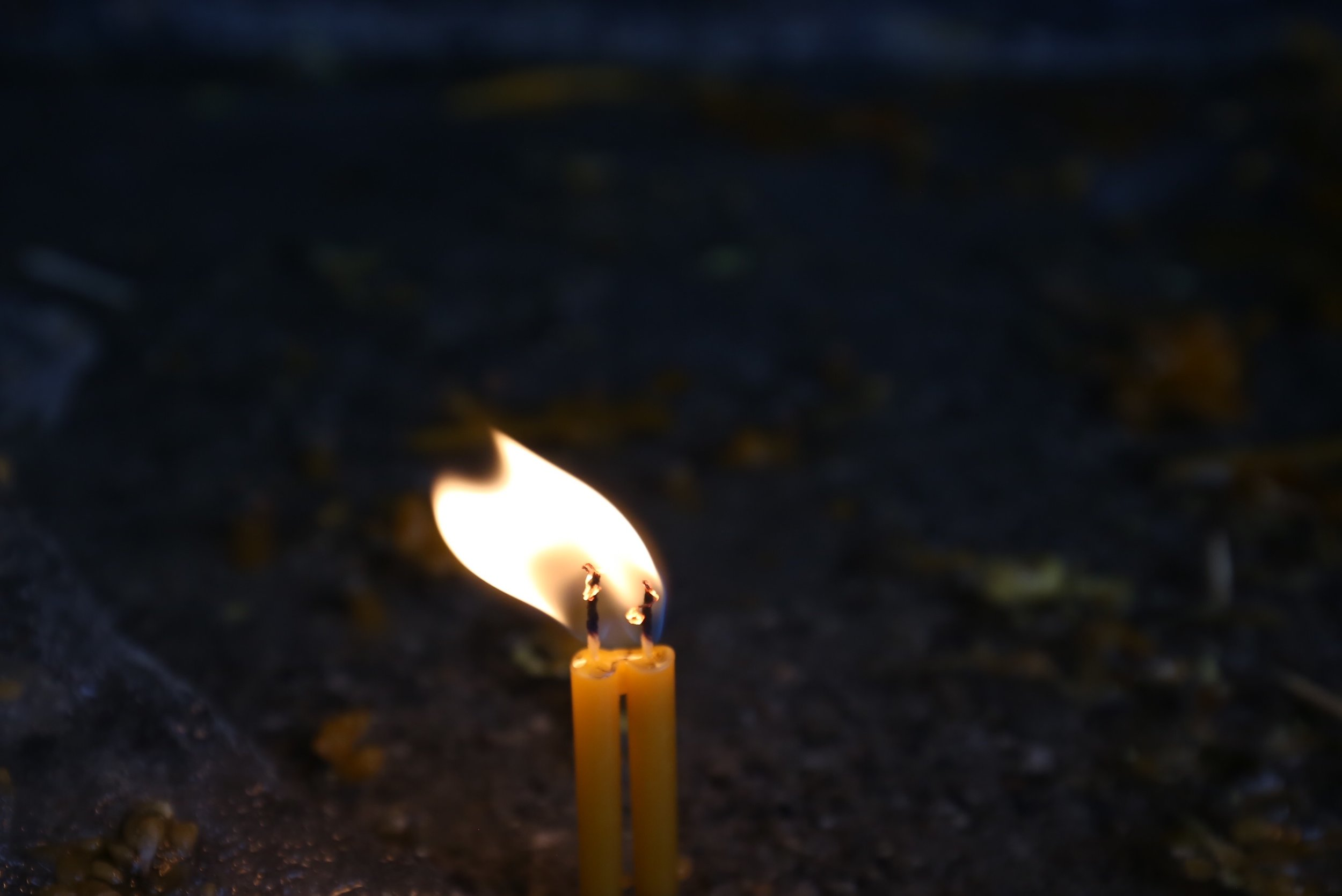 Two flames join from two prayer candles.