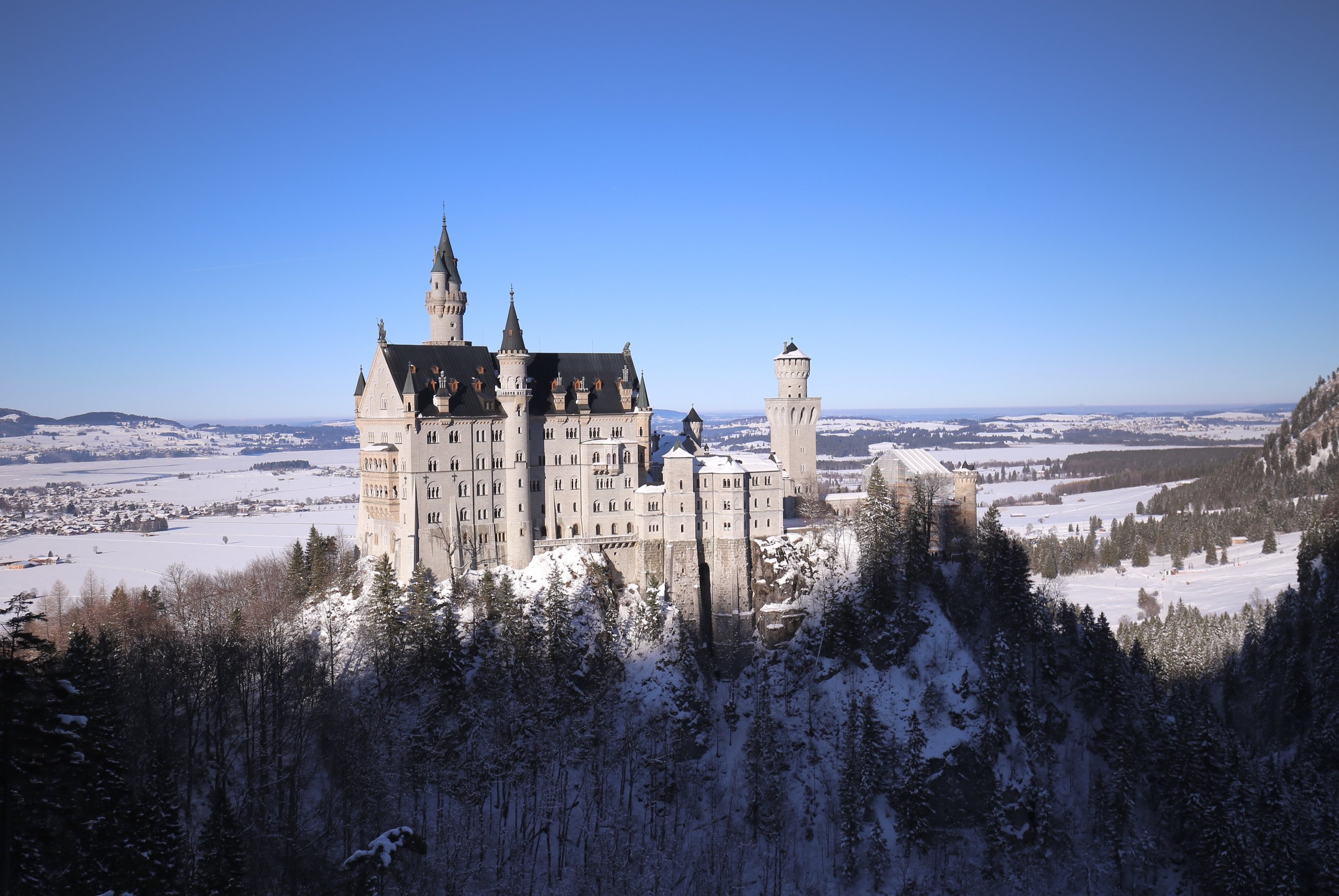 Cinderella's castle - Neuschwanstein castle perched on a rocky cliff surrounded by snow.
