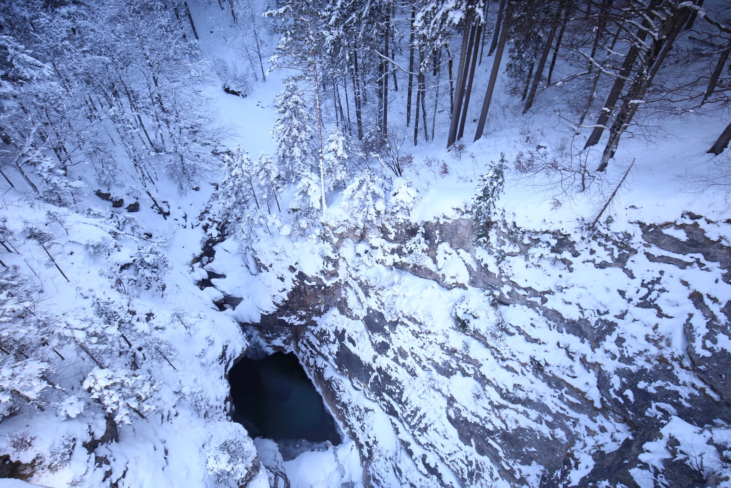 A blue pool sits at the bottom of a snowy crevasse.