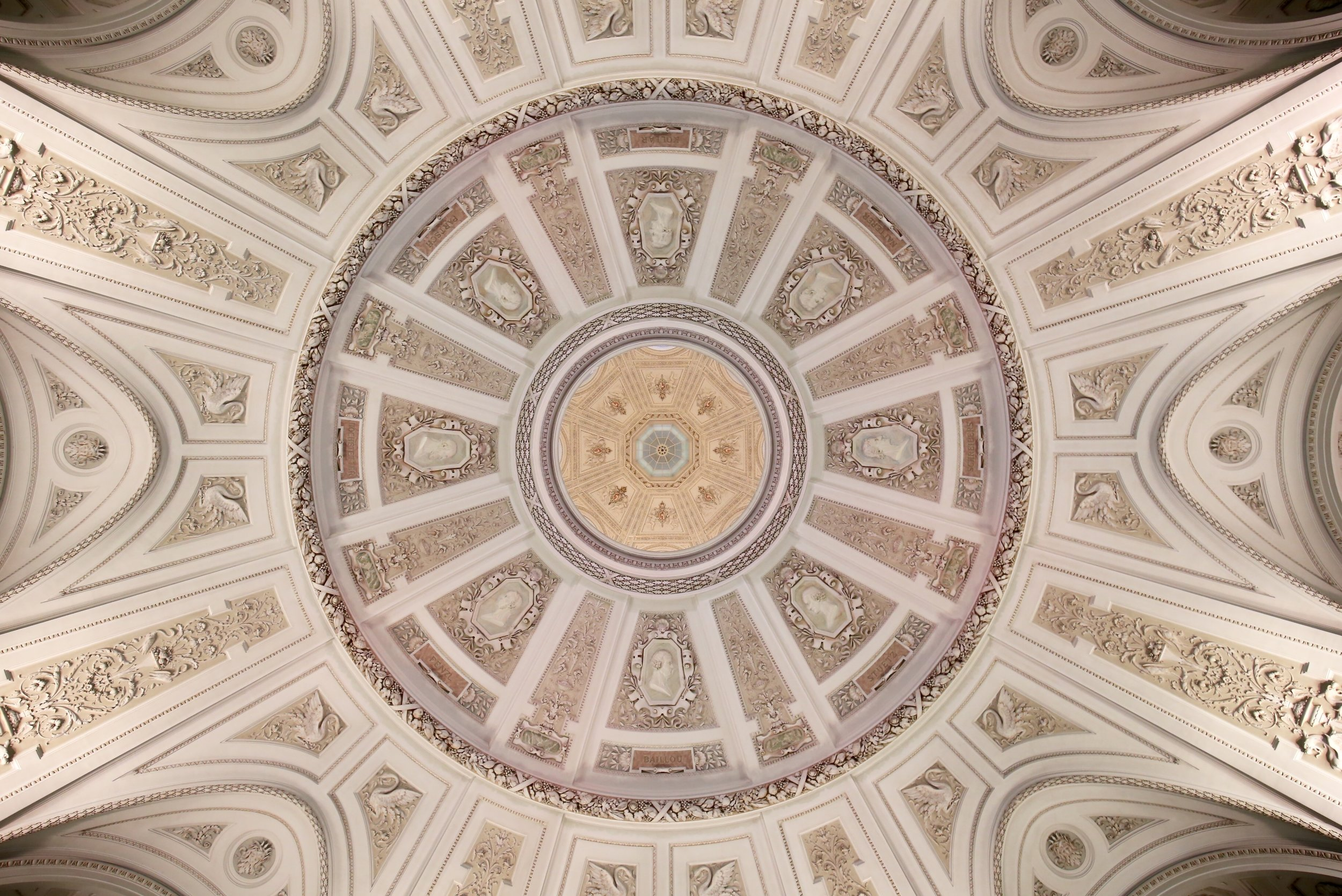 A pink domed ceiling with intricate baroque decoration.