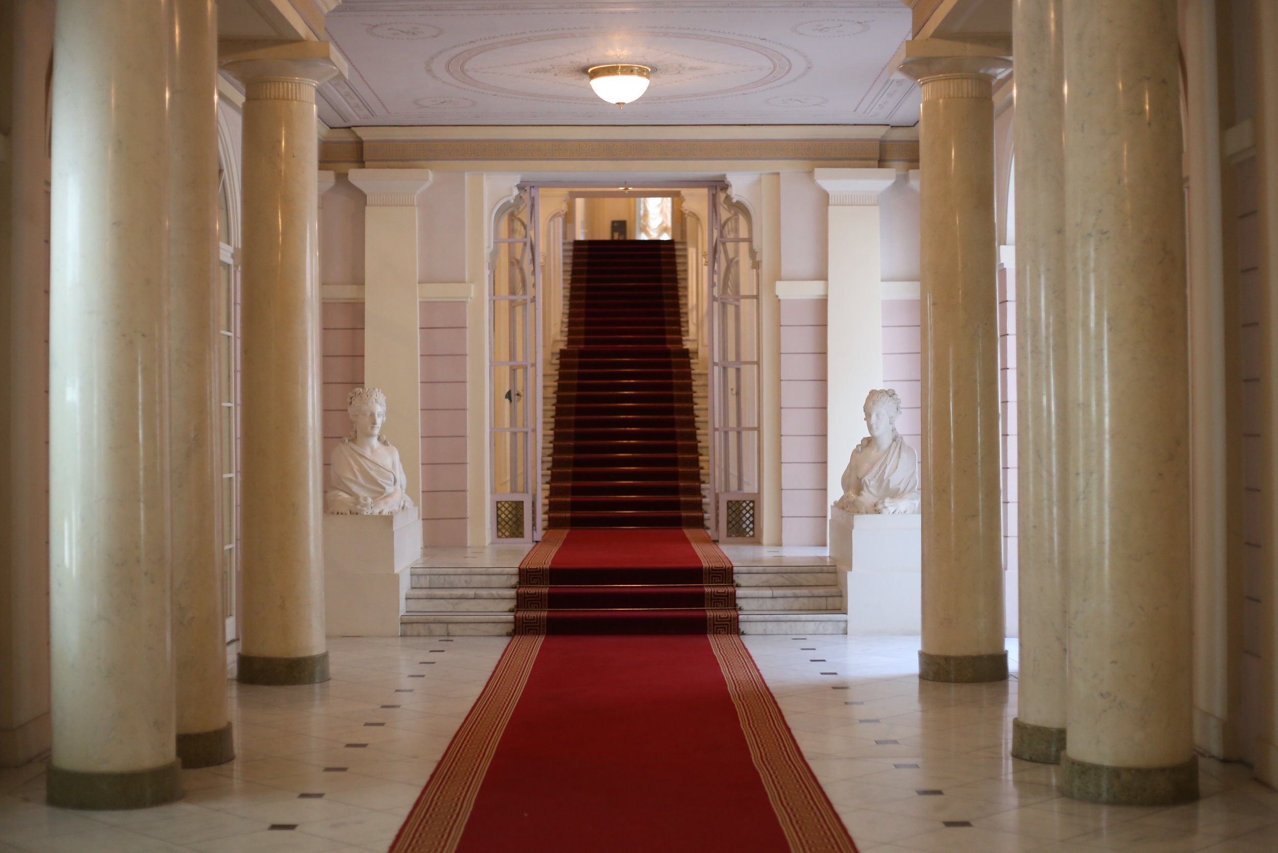 Red carpet in a grand old hallway of pink marble.