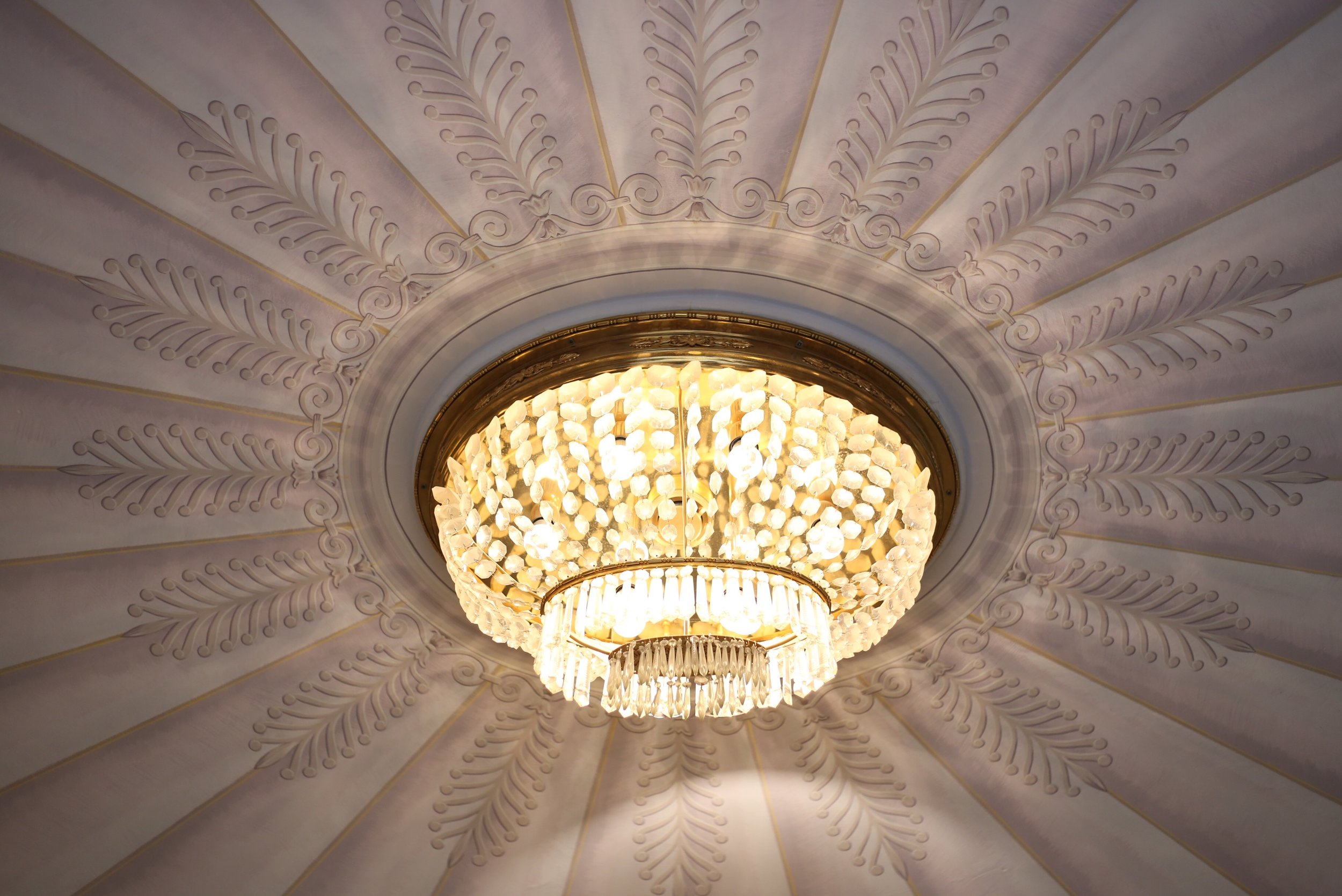 A small crystal chandelier set in the middle of a painted marquee ceiling.