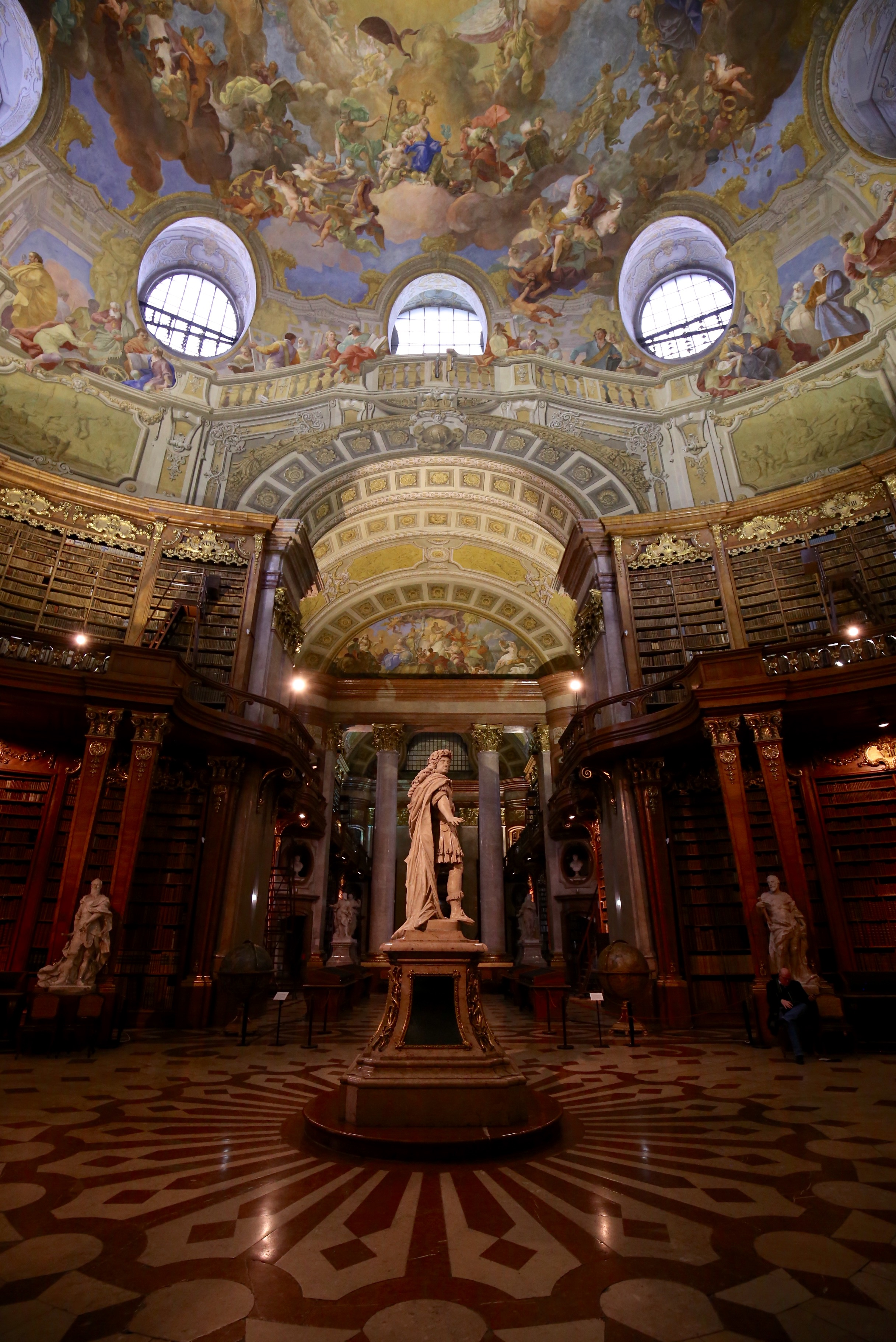 A magnificent old library with a painted ceiling of angels, and marble floors, and books stacked to the roof - The National Archives of Vienna.