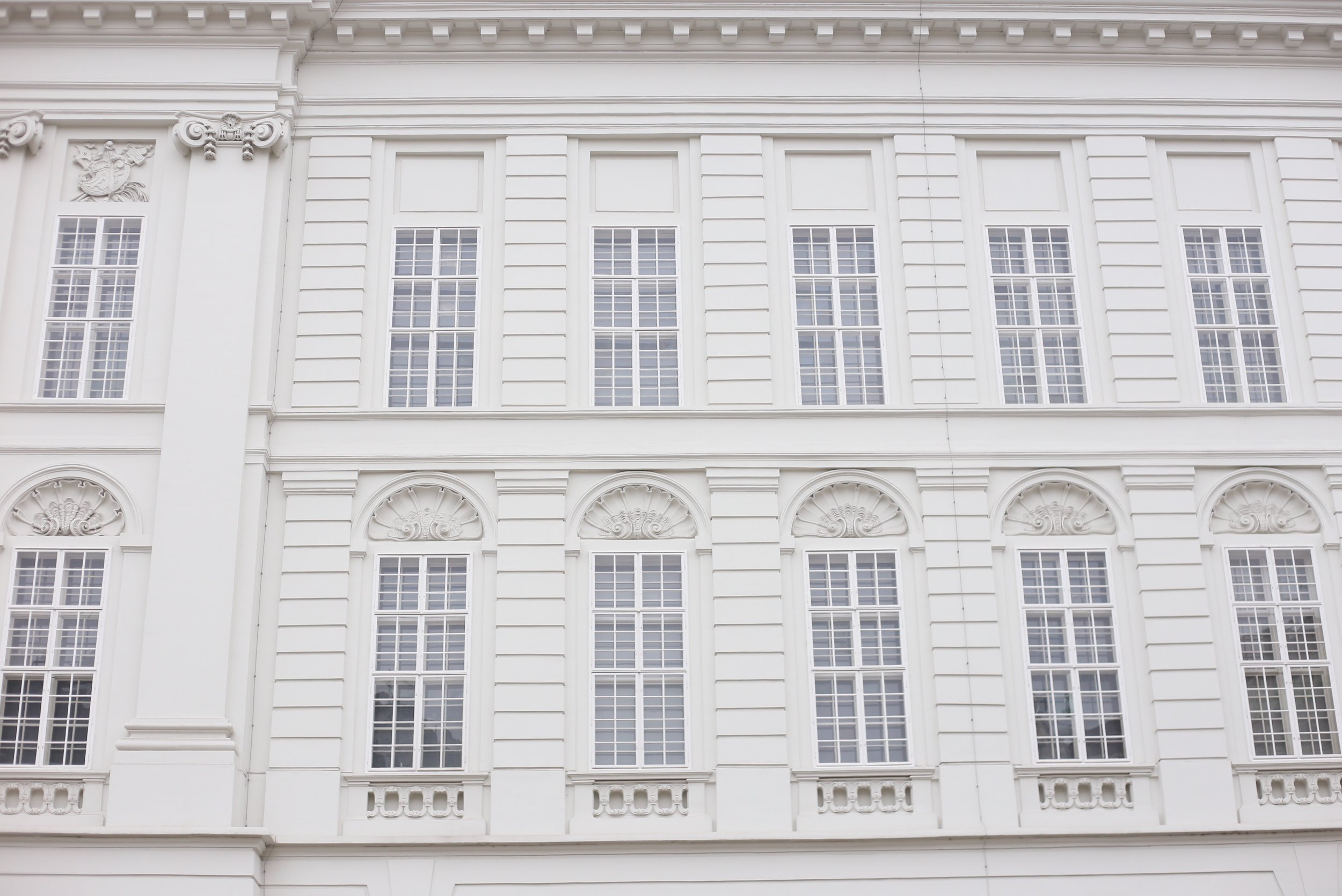 Grand apartments with delicate window decoration all in white.