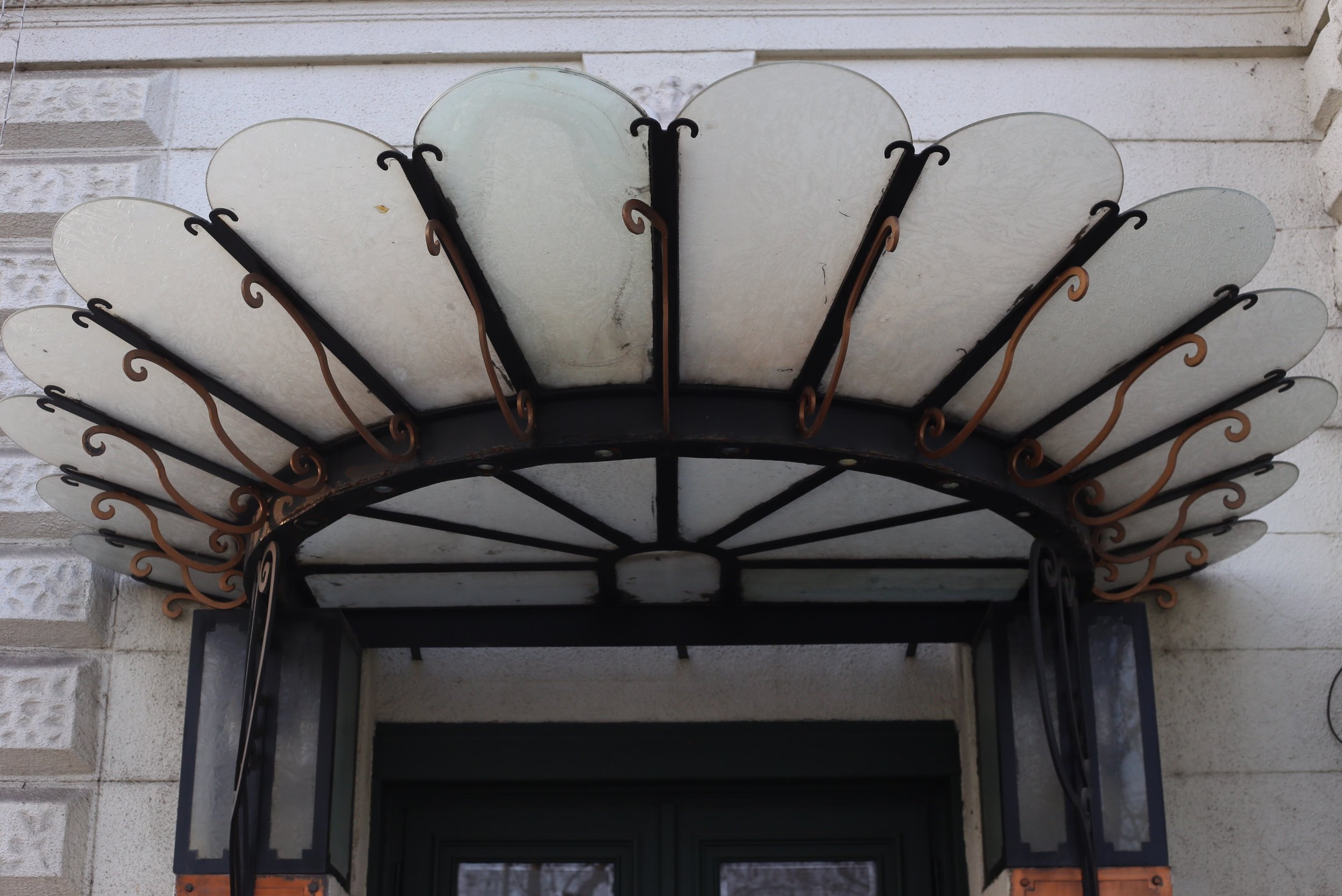 An art-nouveau canopy or awning, made of glass and iron, over a hotel door.