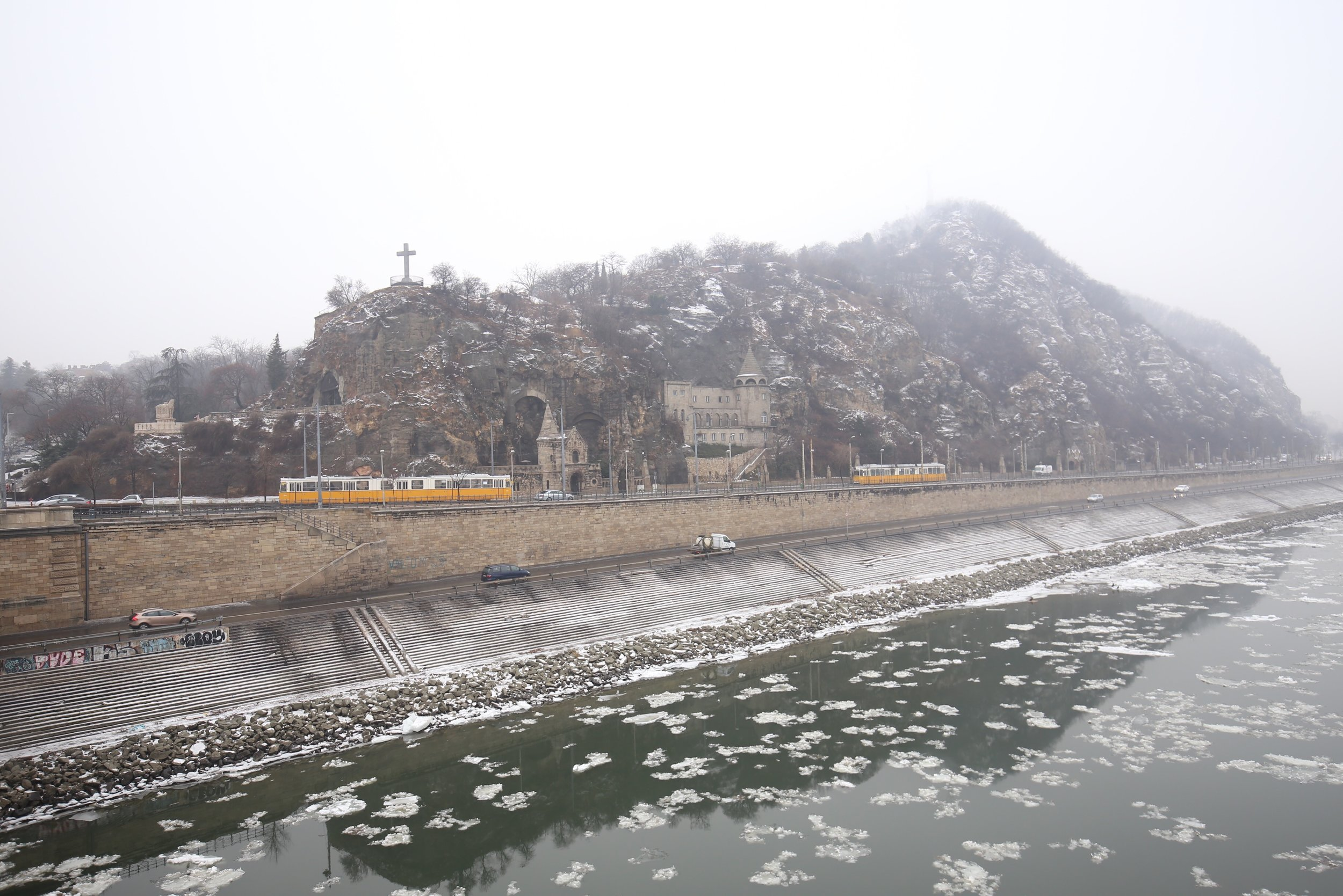 The yellow trolleys of Budapest rattle by the icy Danube river in winter.