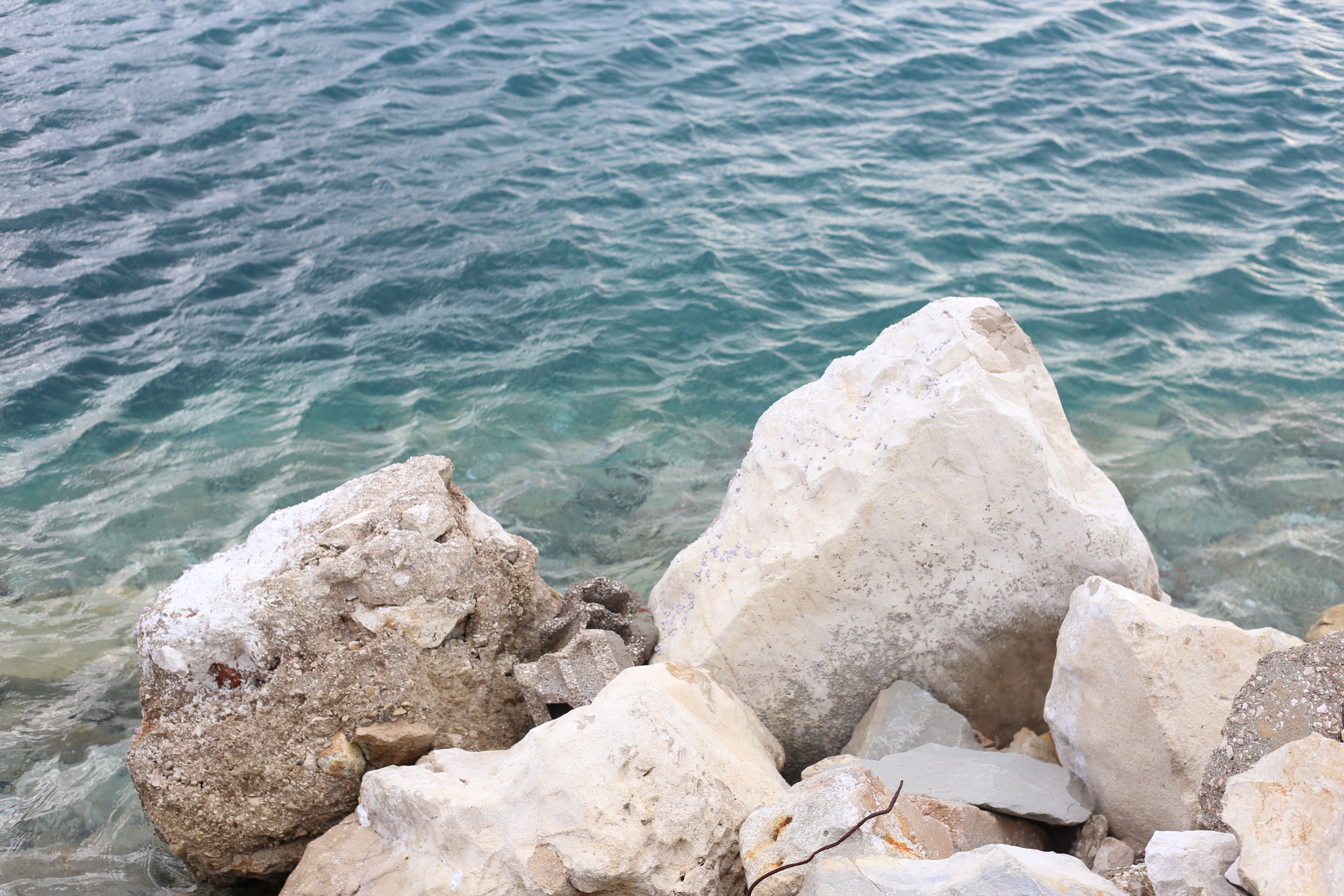 The Adriatic sea with blue waters and white rocks on the Croatian coast.