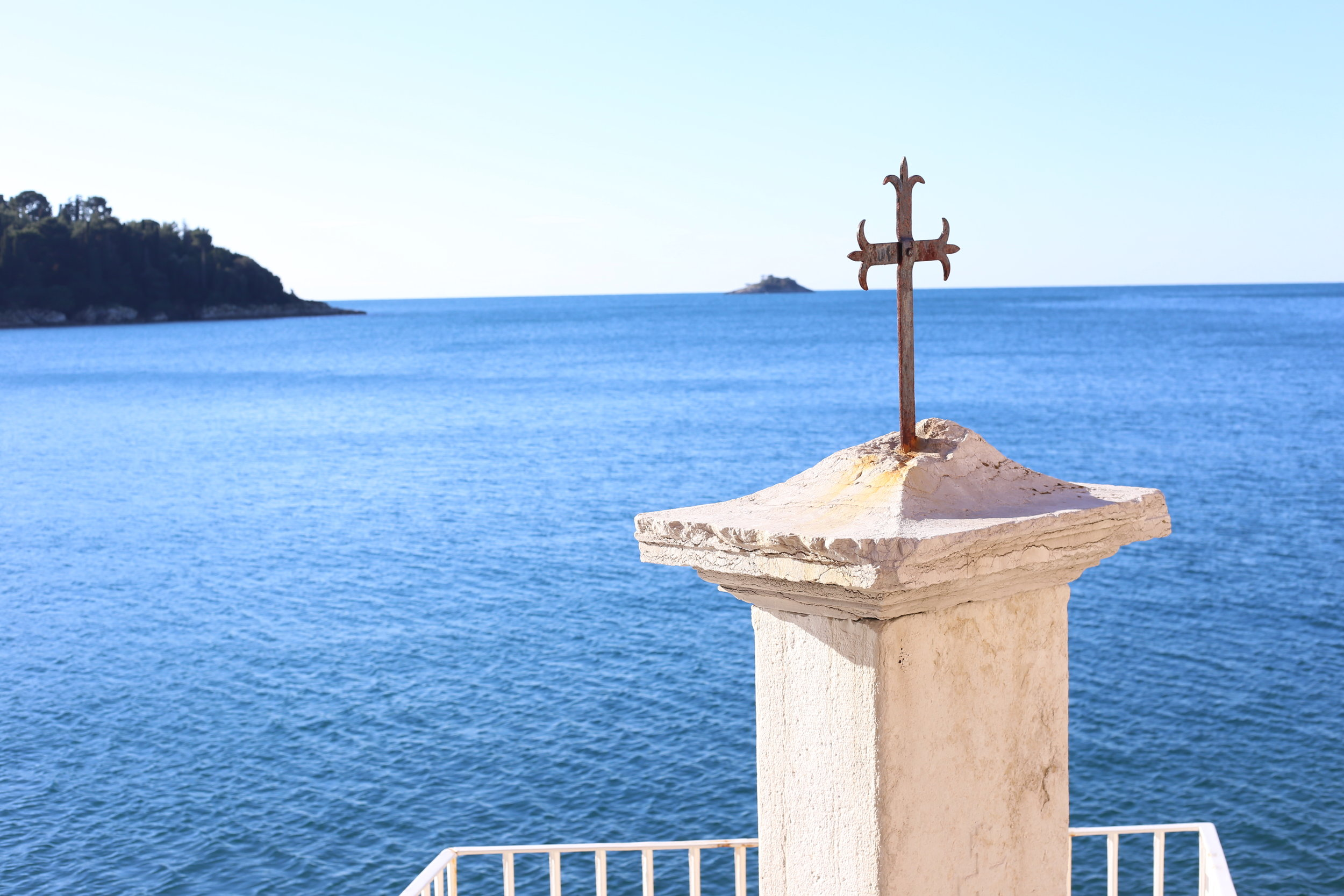 blessings - a cross sits by the sea.