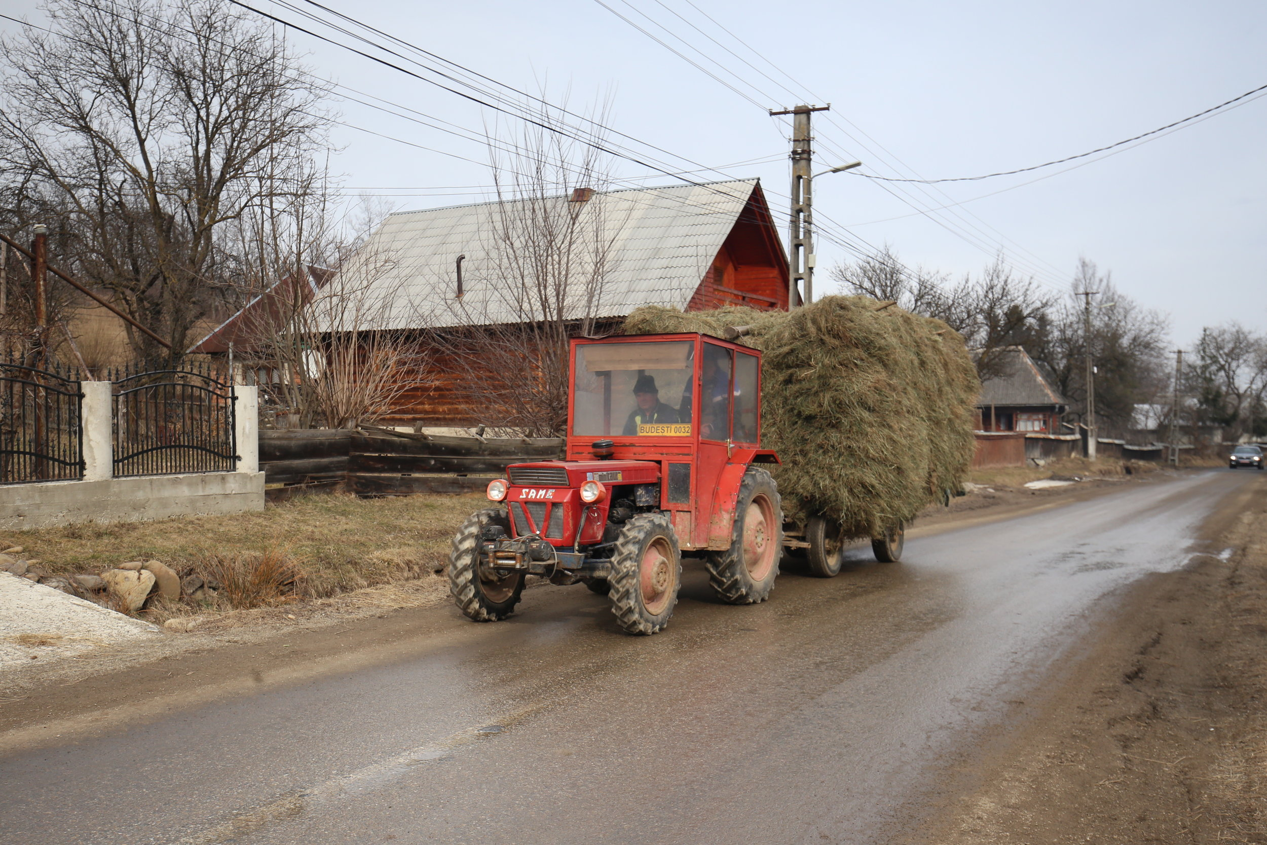 Tractor carrying a huge stack of hay through a small Romanian village.