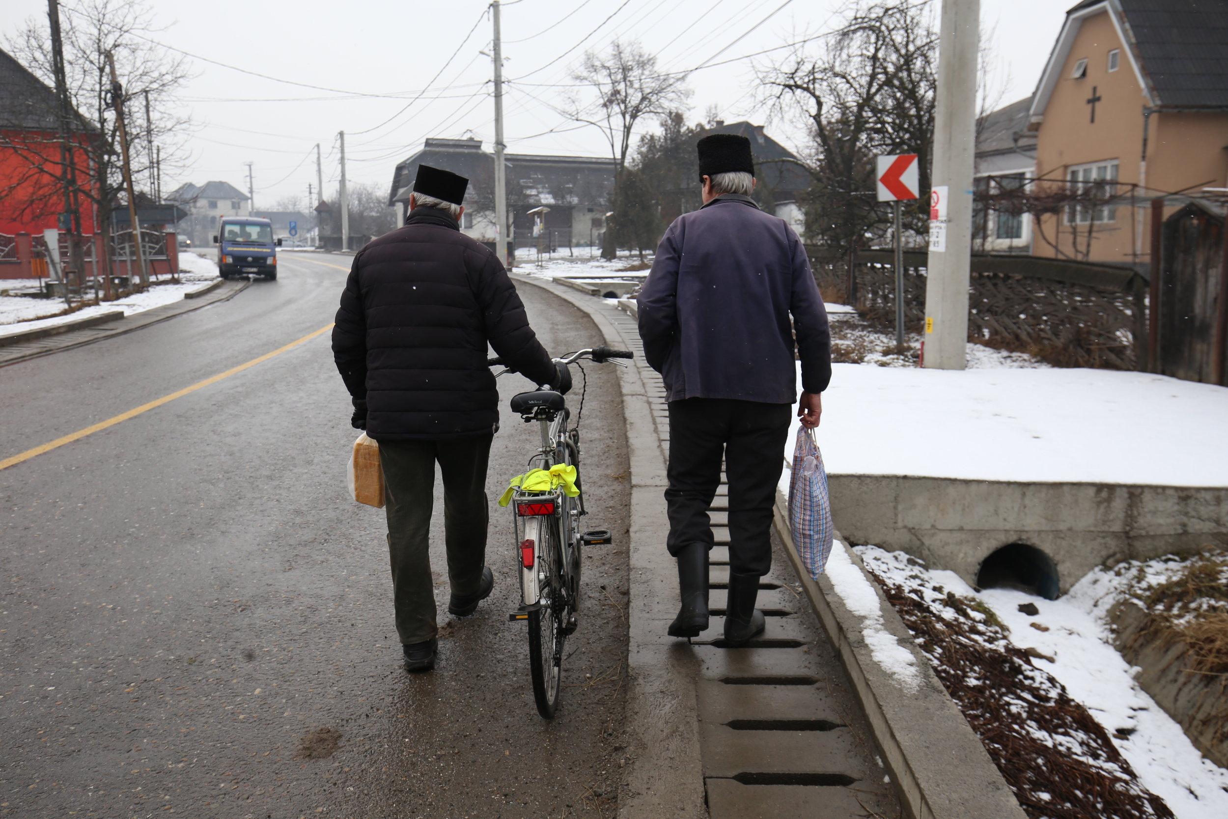 Two Romanian gentleman wandering down the village road - with fuzzy hats on.