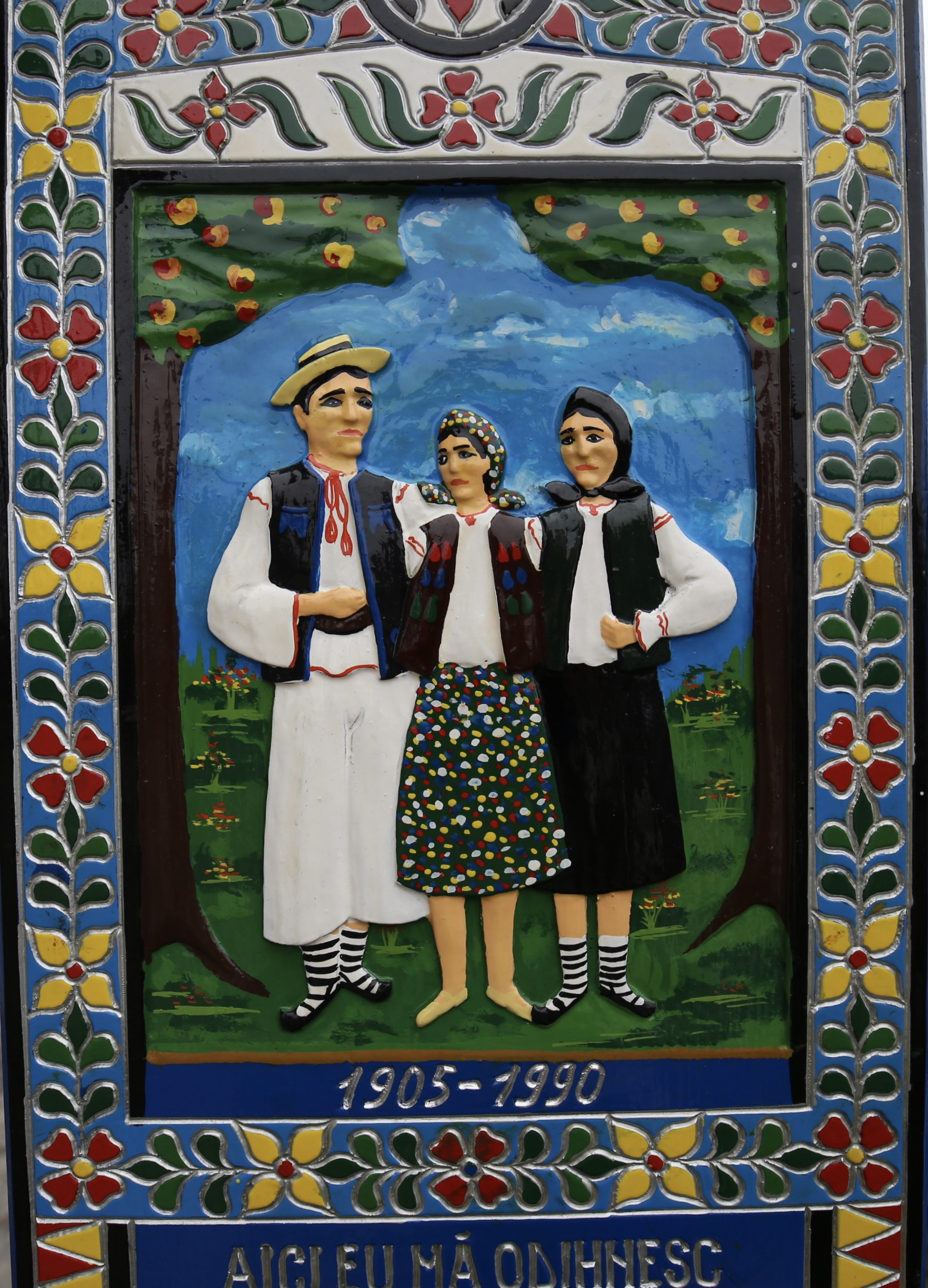 A grave marker in the Merry Cemetery - showing a colourful painting of a farming family.