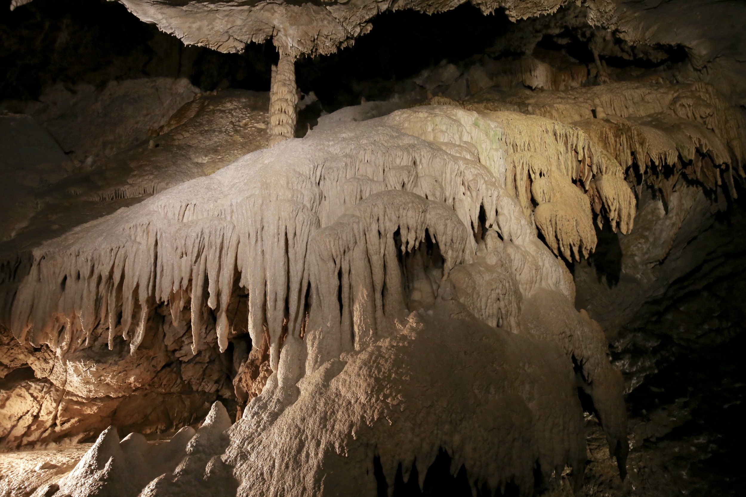 White calcium limestone waterfall in an underground cave - with unicorn horn stalagmites.