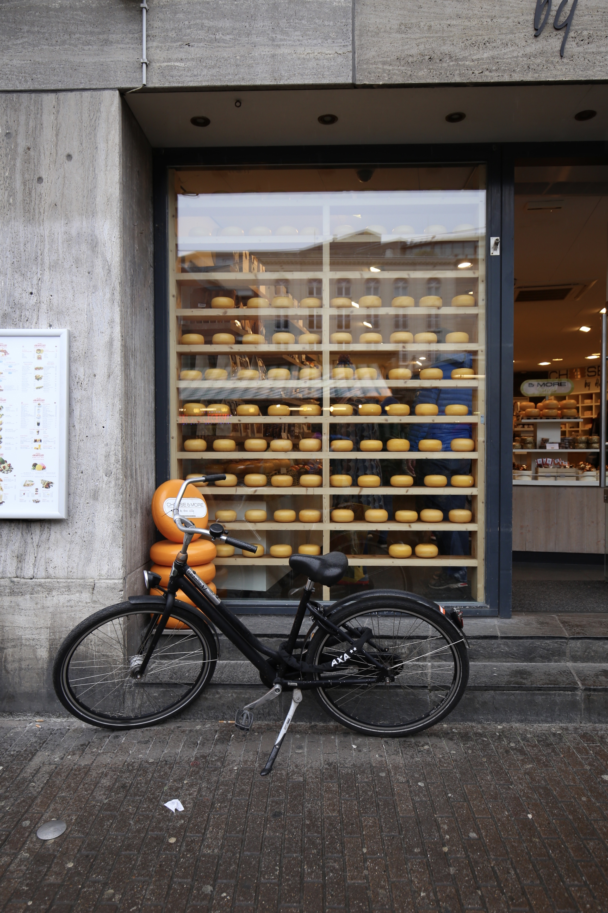 Rounds of cheese in a shop window, with a bike outside, Amsterdam.