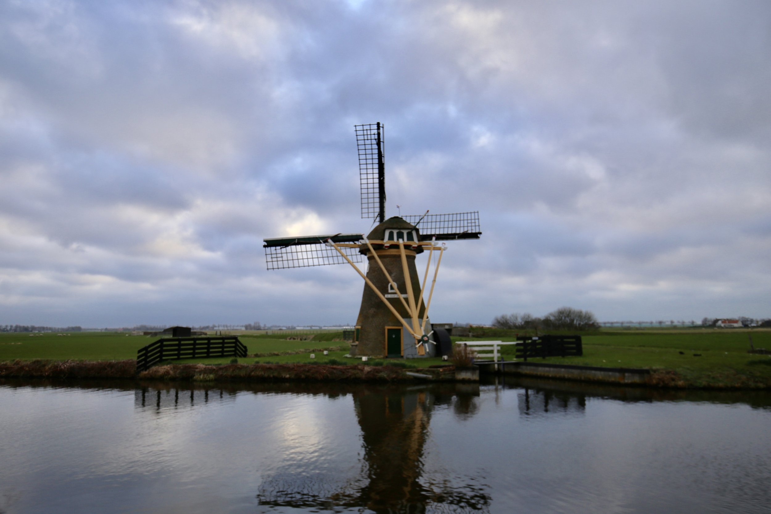 A dutch windmill by the canals at dusk.