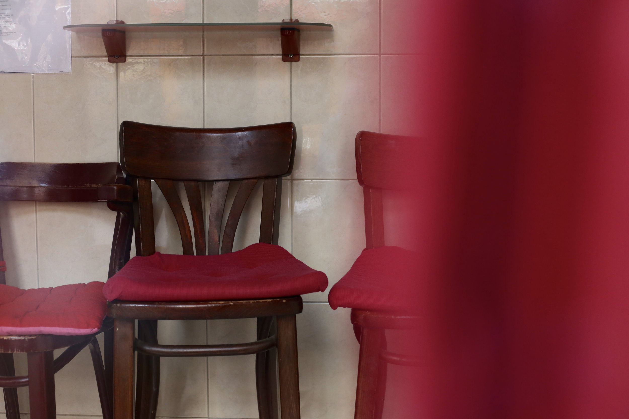 An empty red chair in a window of the Red Light District, Amsterdam.