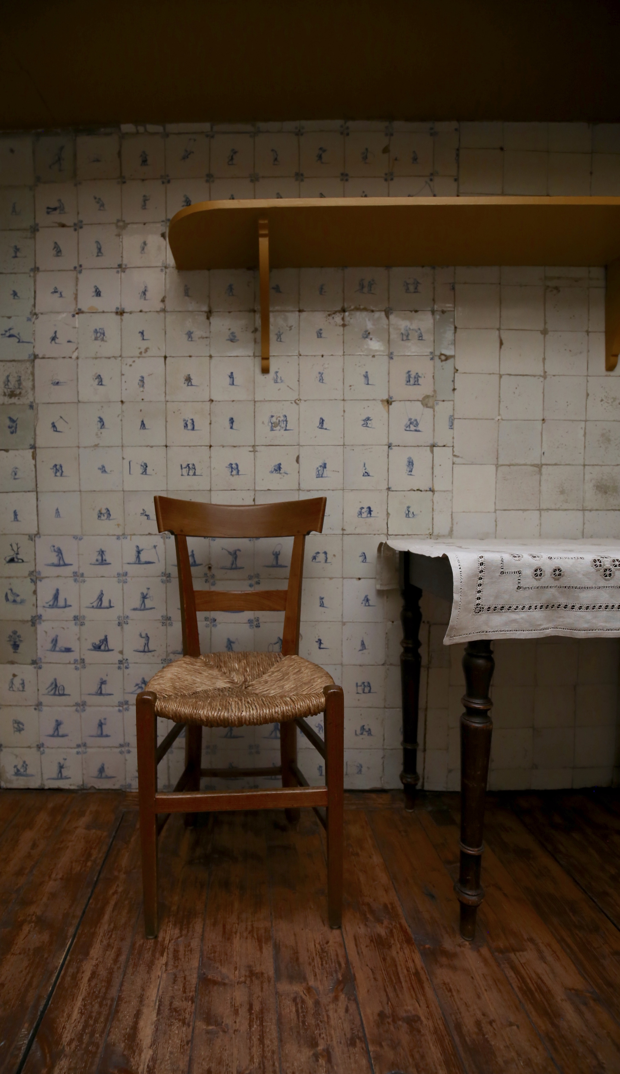 A beautiful old wicker chair in a dutch tiled kitchen - homes like a painting.