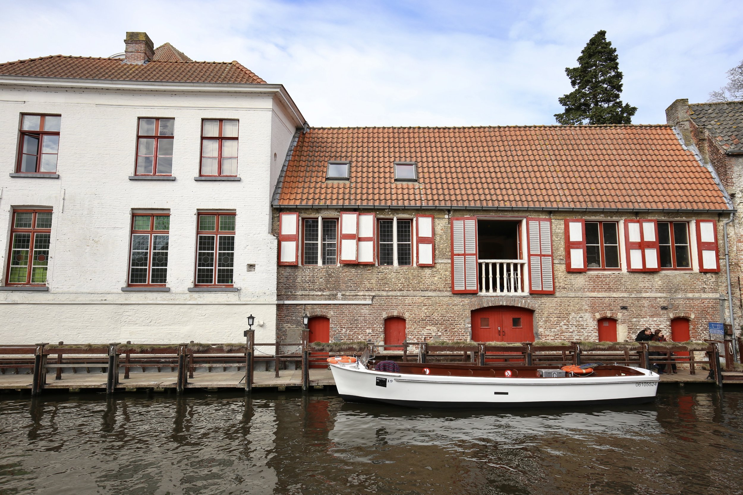 A brick house with red shutters and a small boat in the canal.