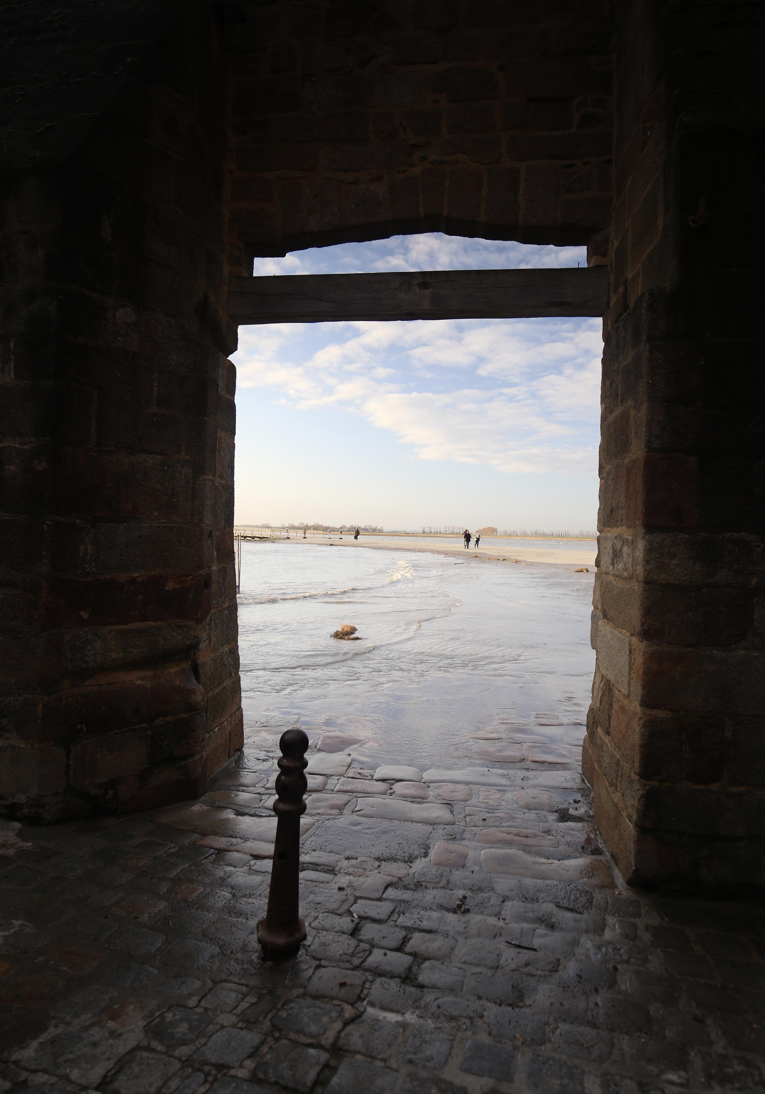 The high tide at Mont Saint Michel - with waves lapping at the stone door to the island.