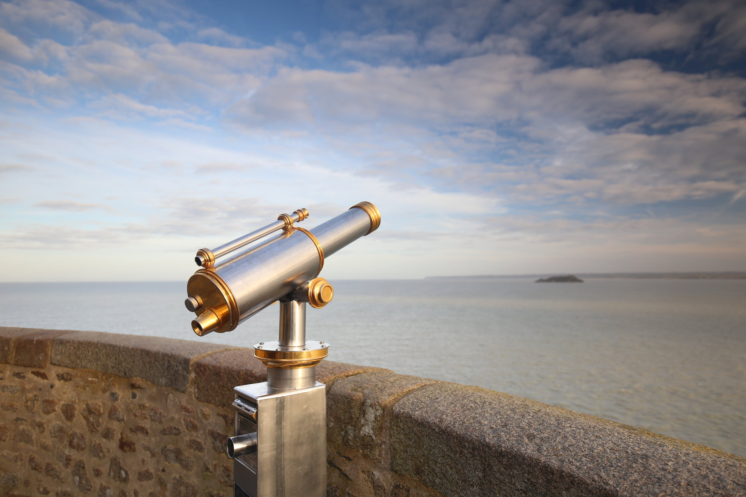 A silver telescope looking out over the sea from the stone walls of Mont Saint Michel.