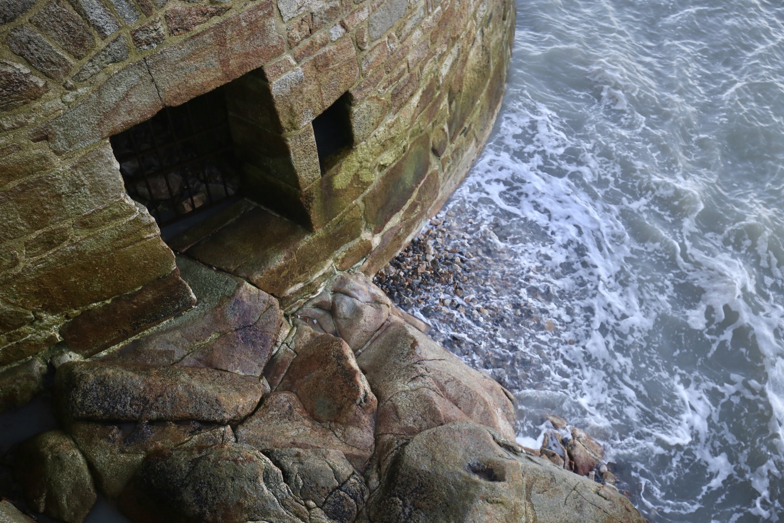 Waves of the sea on a medieval island - a castle door by the sea.