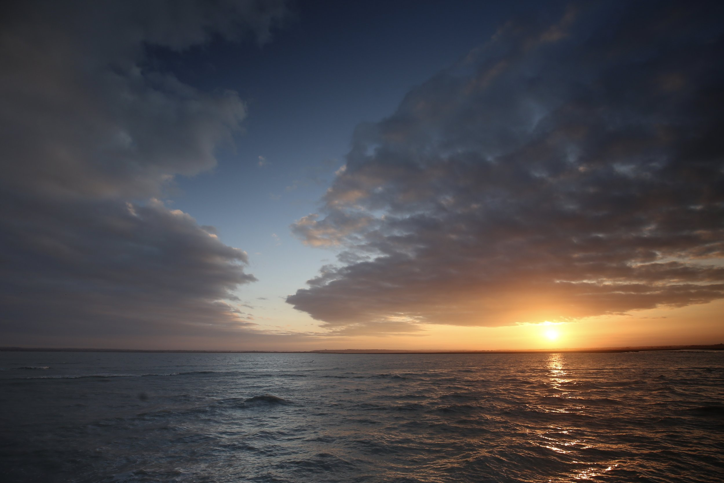 Sunrise over the sea with a break in the clouds.