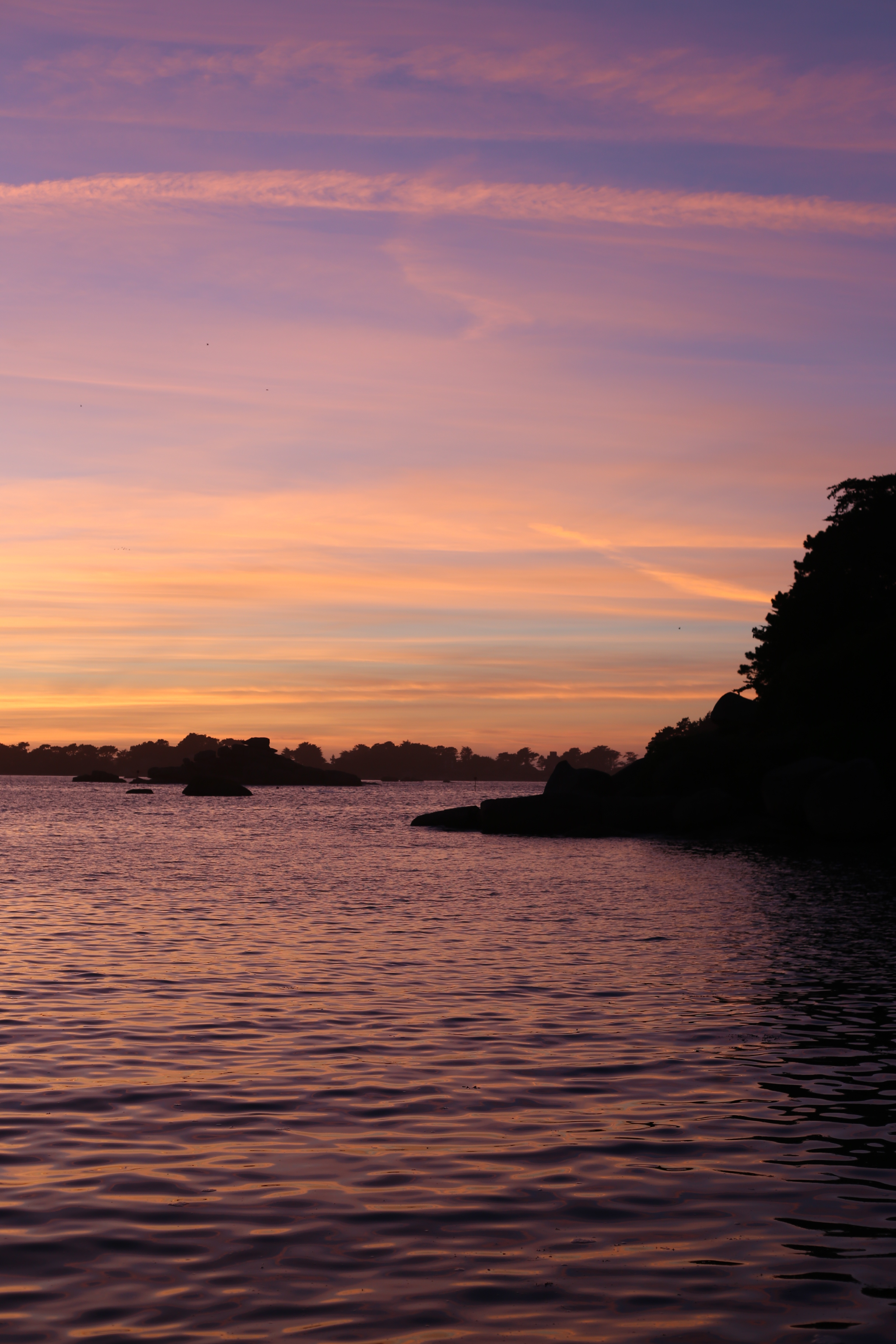 Beautiful purple and pink and orange sunset on the coast of Brittany, France.