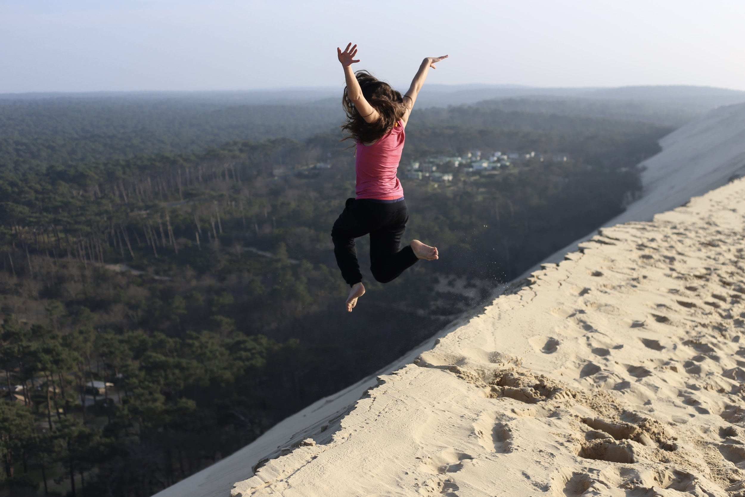 Leaping into the unknown - jumping off the edge of Dune du Pilat, France.
