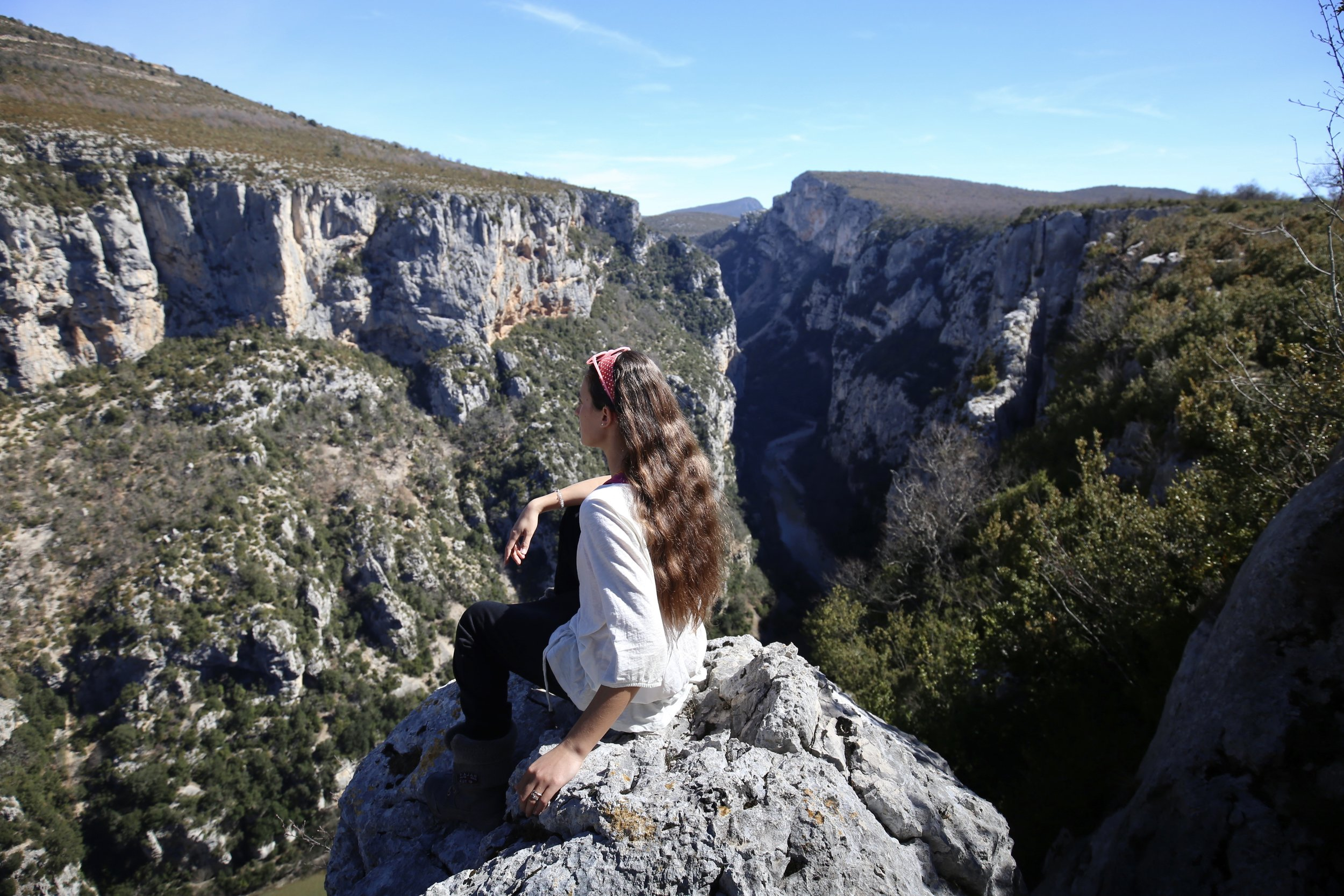 Sitting on the edge of the Verdon Gorge, looking out over the river far below in the canyon.