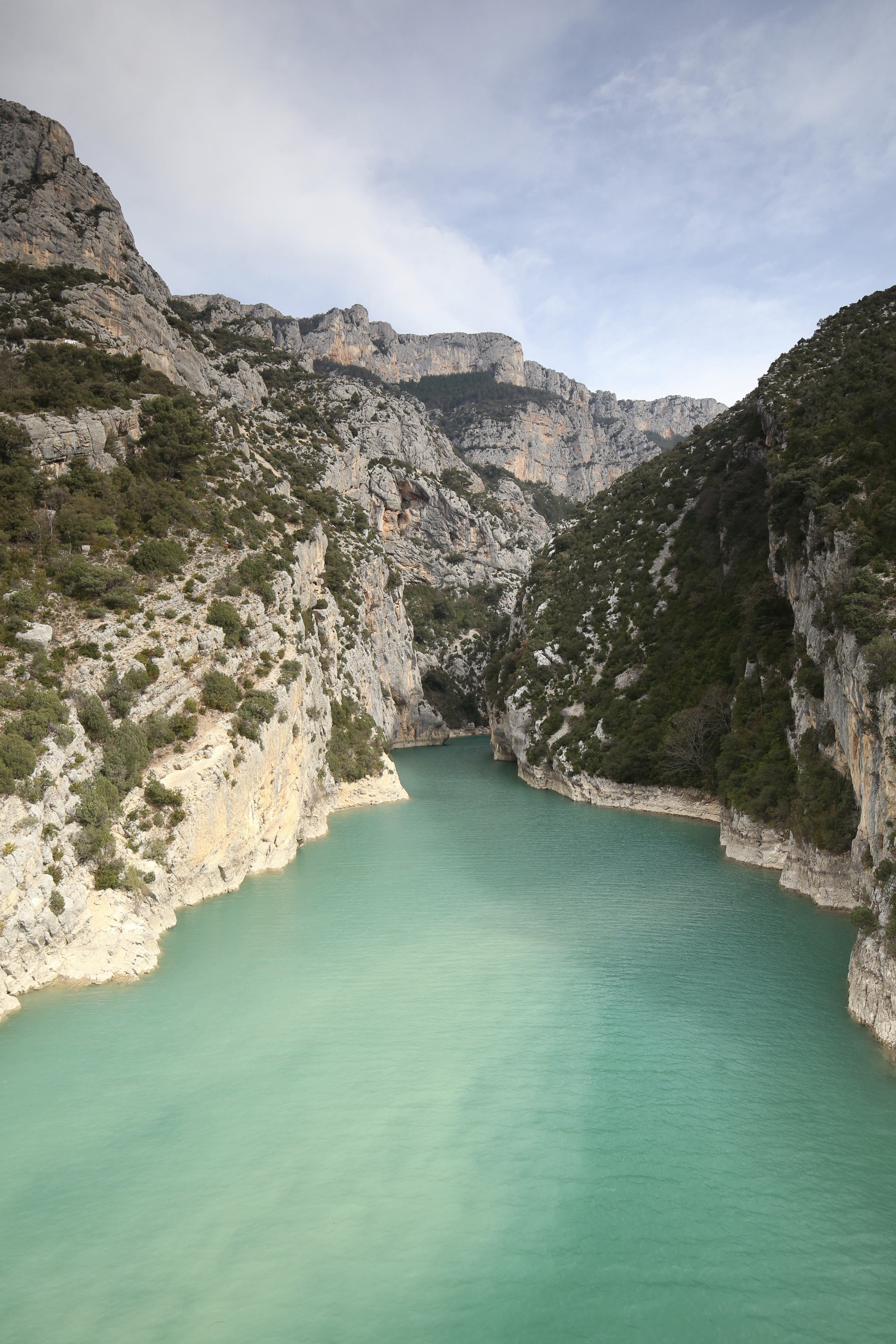 The turquoise river runs through the white rock of the Verdon Gorge, on a sunny day.