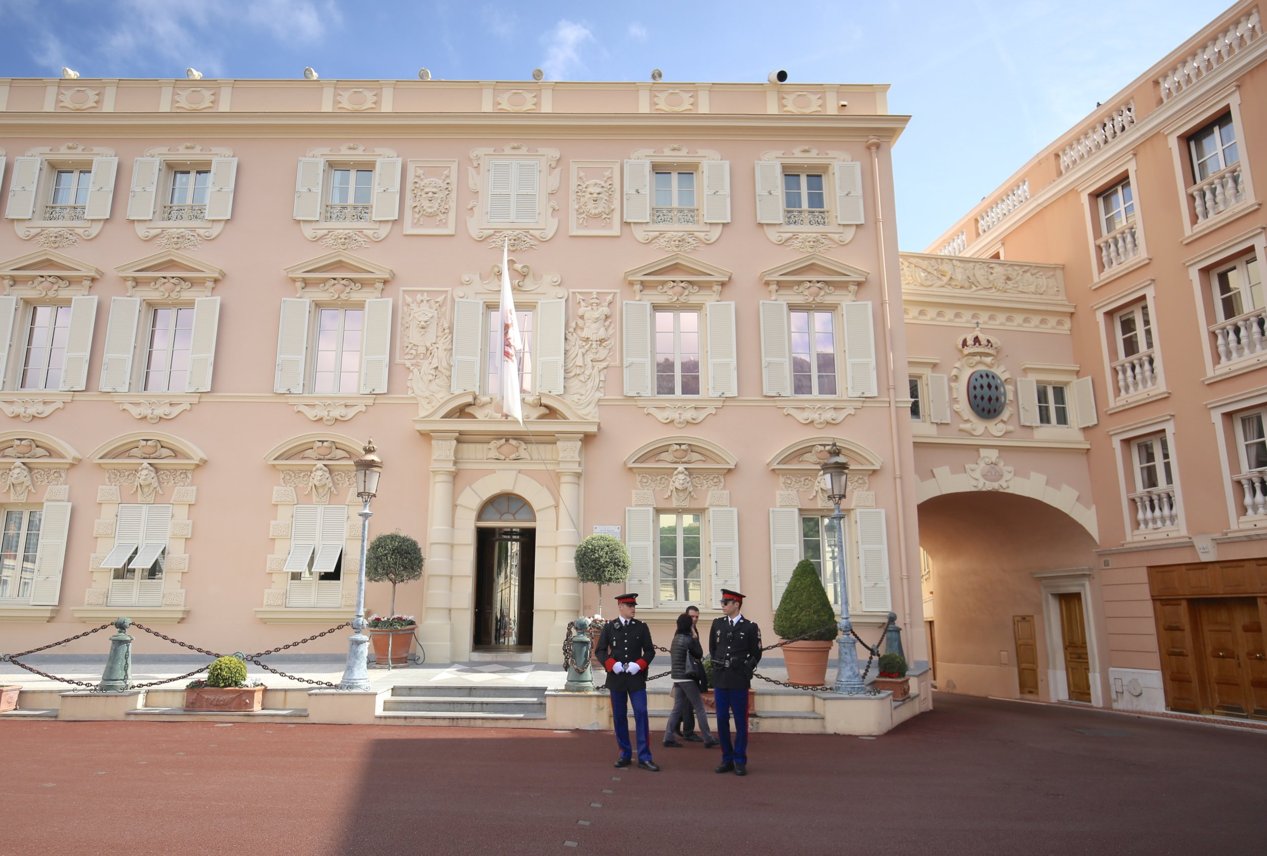 Royal police hang around a perfect pink cookie cutter building, Monaco.