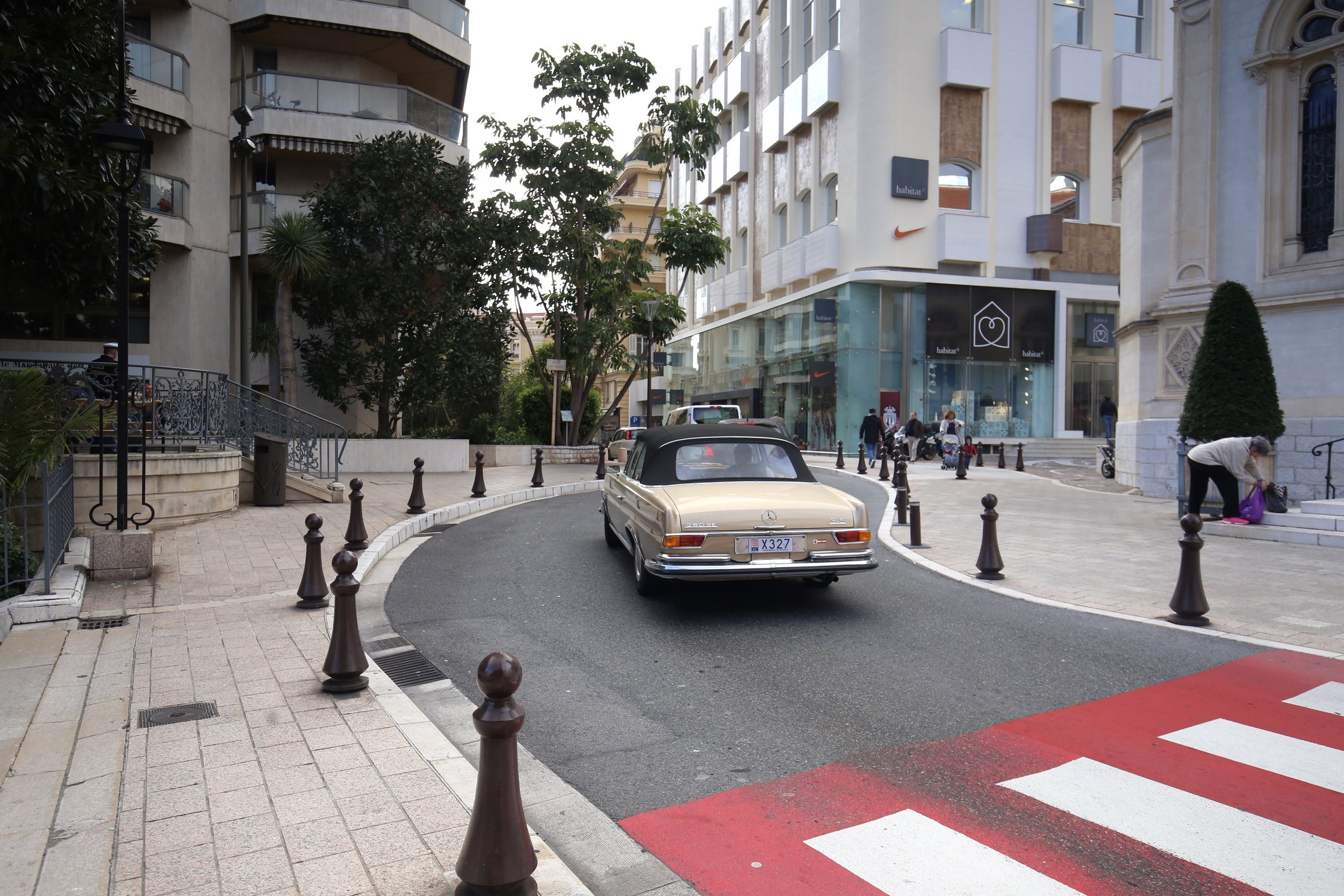 A fancy old car driving through the streets of Monaco.