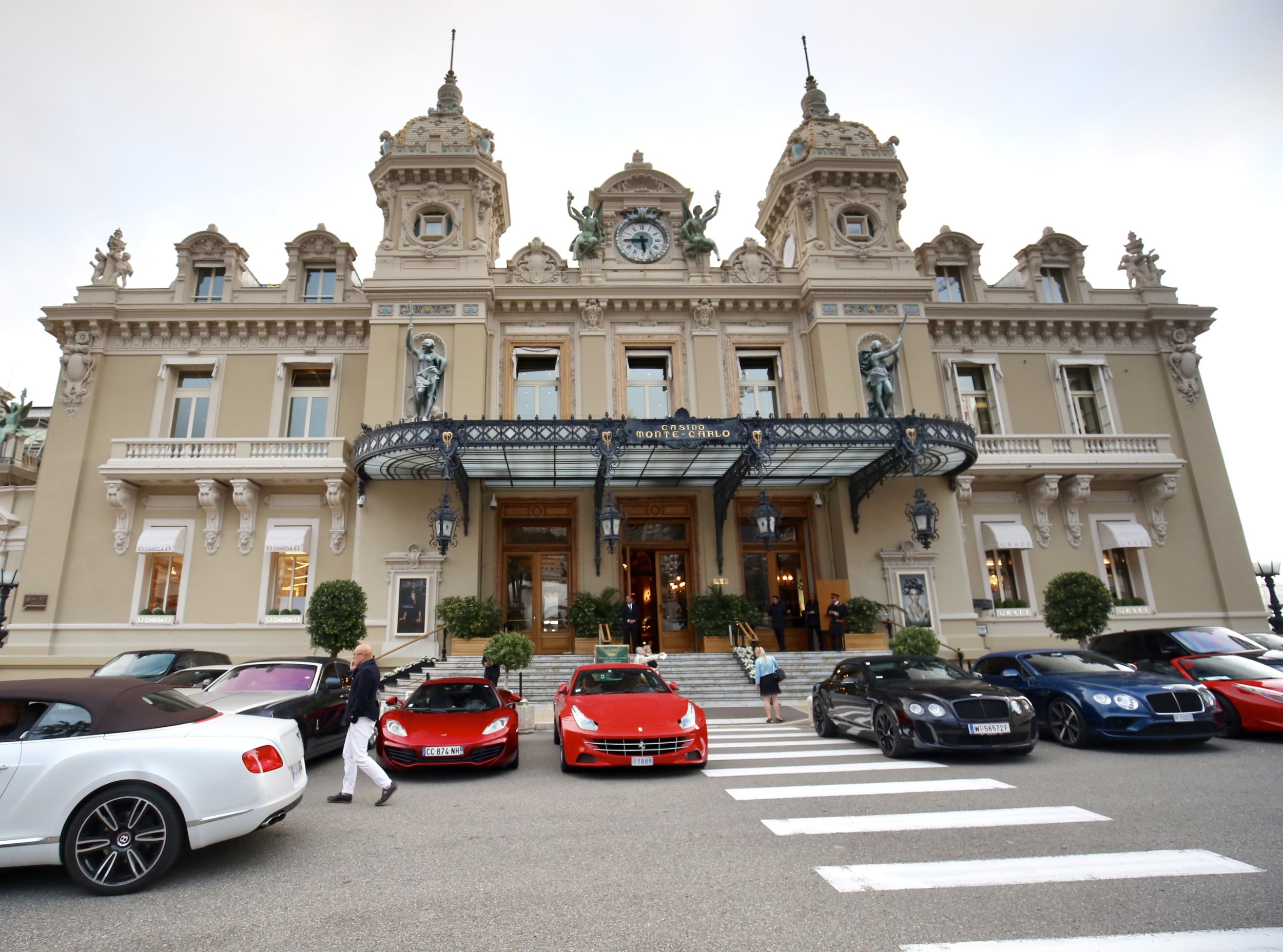 The Monte Carlo Casino façade, with luxury cars parked in front.