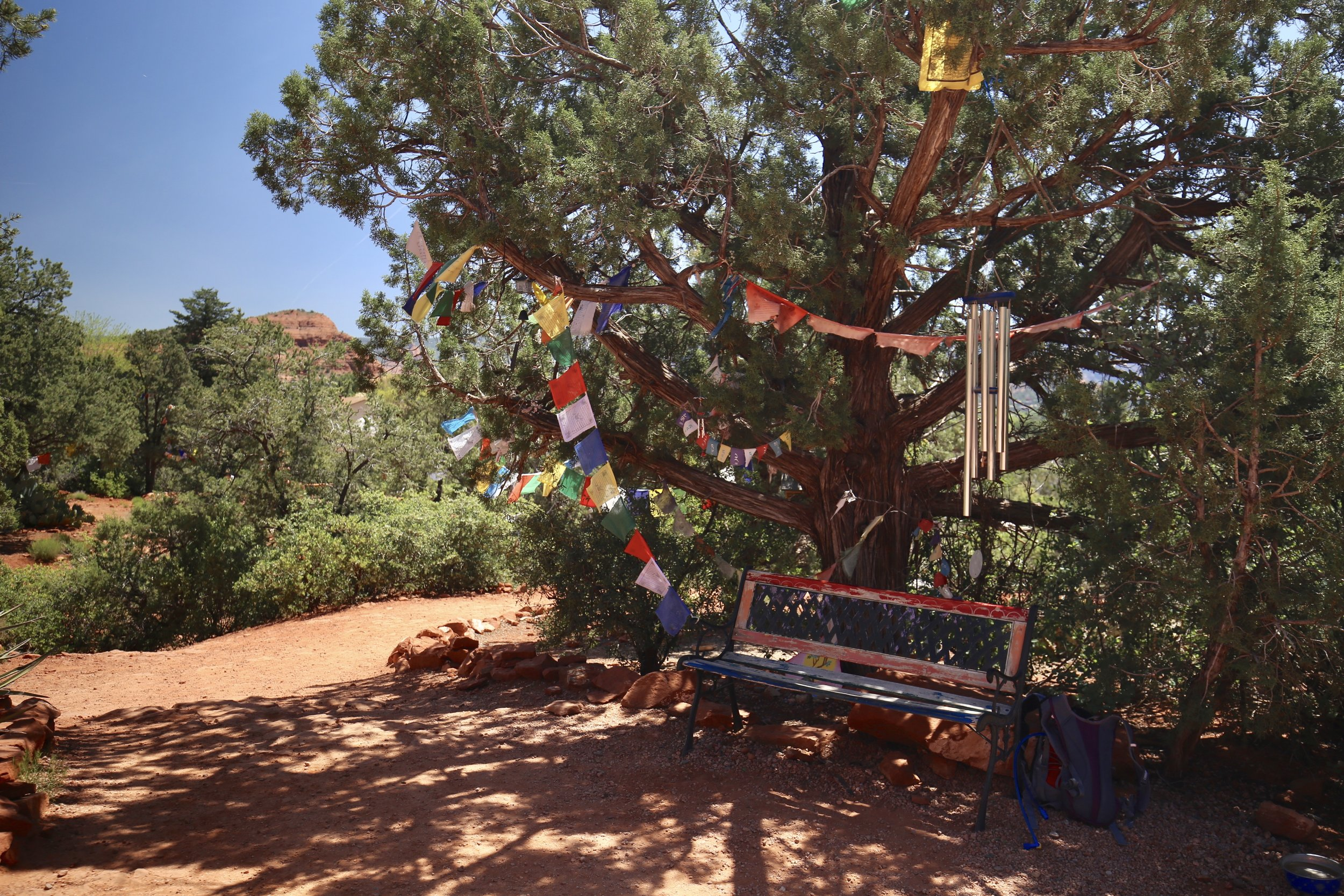 A seat and prayer flags in the gardens of the peace stupa, Sedona.
