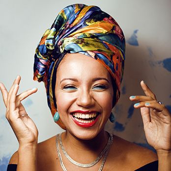 woman smiling with green nails and a bright scarf