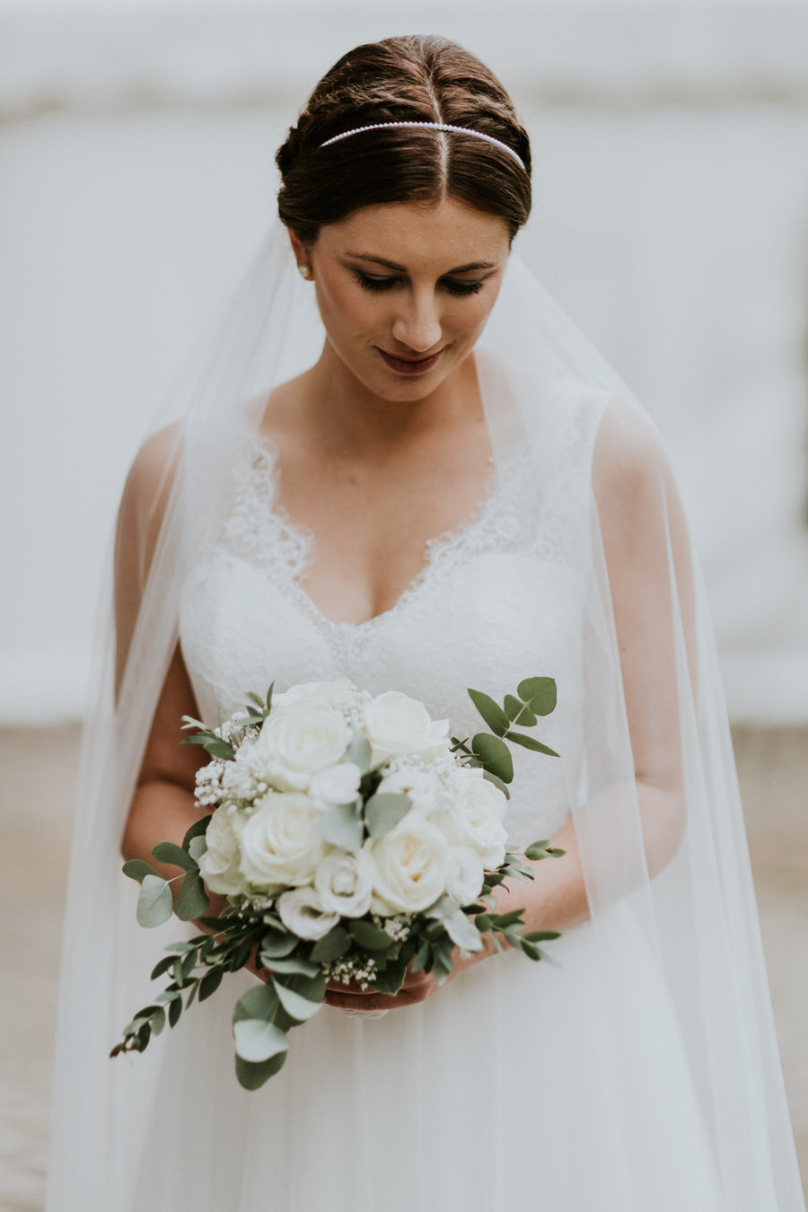 Braut schaut ihren Blumenstrauß an