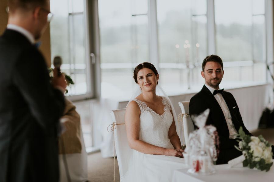 Brautpaar schaut den Freuend bei seiner Rede an
