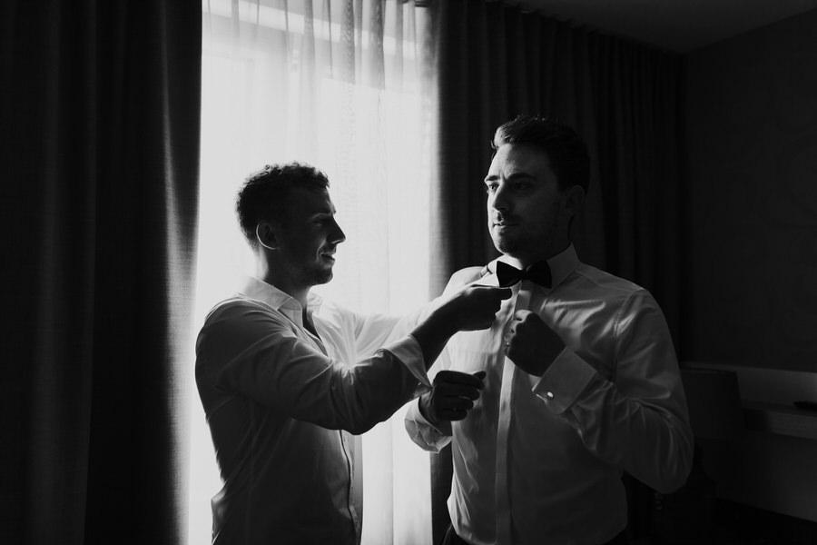 Trauzeuge hilft Bräutigam beim Fliegeanlegen