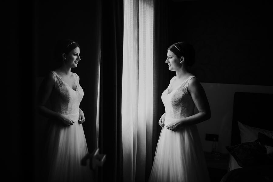 Braut wird in der Glastür reflektiert während sie aus dem Fenster schaut