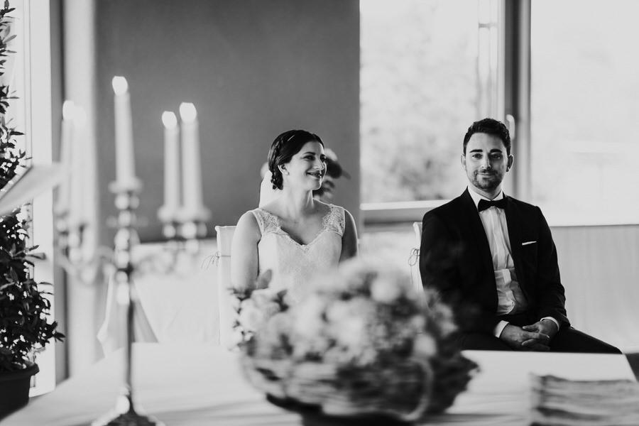Braut schaut den Bräutigam während der freien Trauung vor dem Kerzenständer lachend an