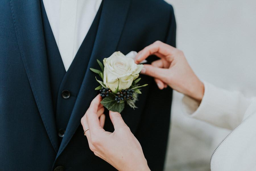 Braut steckt die Blume ein.