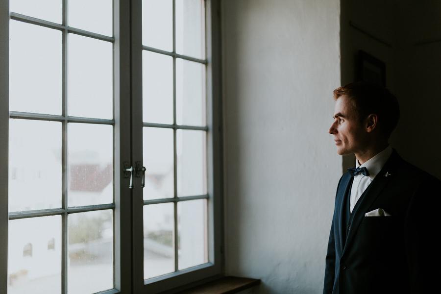 Braeutigam schaut aus dem Schlossfenster